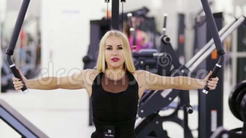 Beautiful female bodybuilder is performing exersices at the gym  Strong  arms, endurance, fitness
