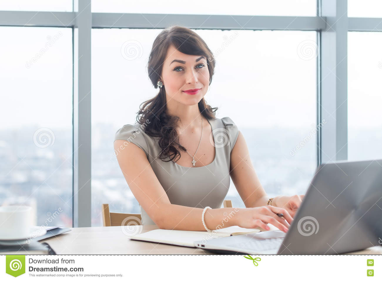 Beautiful female copywriter sitting in office, typing new article, working with text, using laptop at workplace.