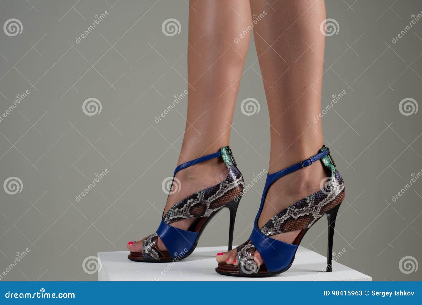 Beautiful female feet in stylish blue high-heeled sandals