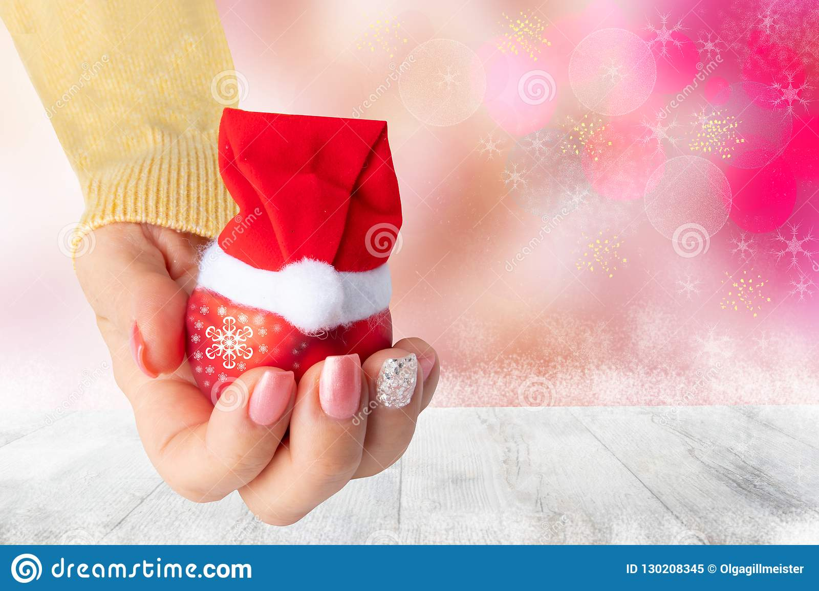 Beautiful female hand with christmas nail design. Hand with elegant pink nail manicure holding a red christmas decoration ball wi