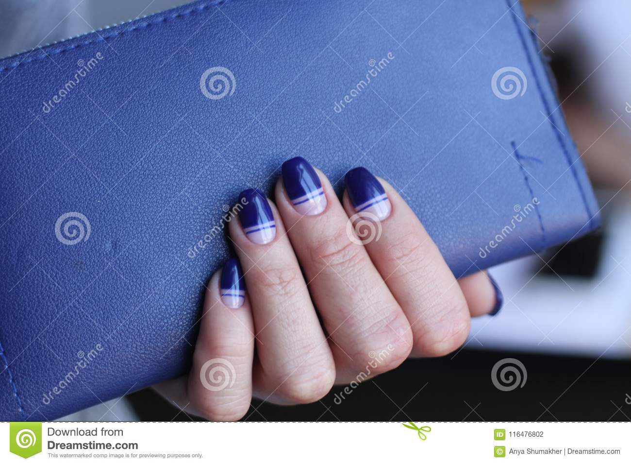 Beautiful Female Hand With Manicure Holds Leather Clutch Dark Blue