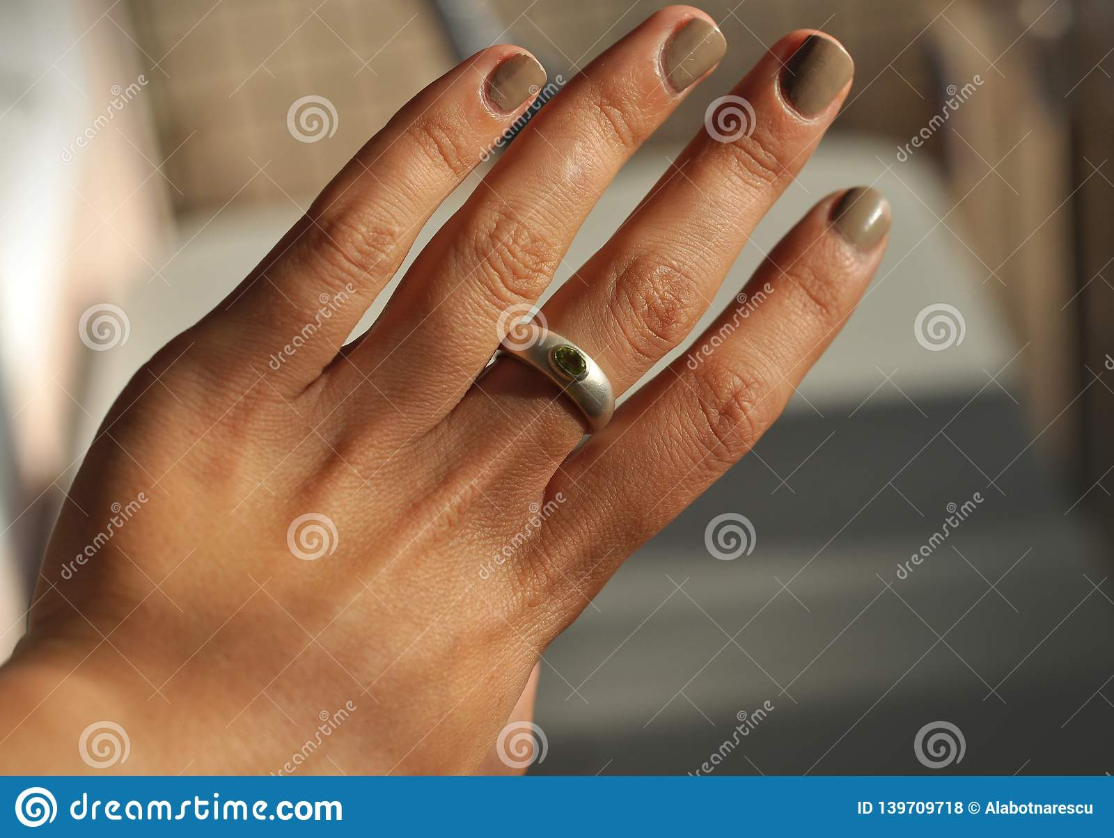 A beautiful female hand with ring. A silver ring chrysolite rock, sign of energy