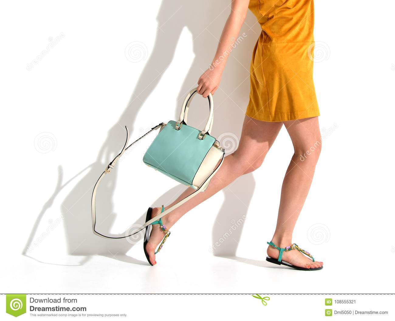 45f4bb75 Beautiful female legs wearing summer shoes in brown yellow designers dress  and blue mint woman clutch bag on white background