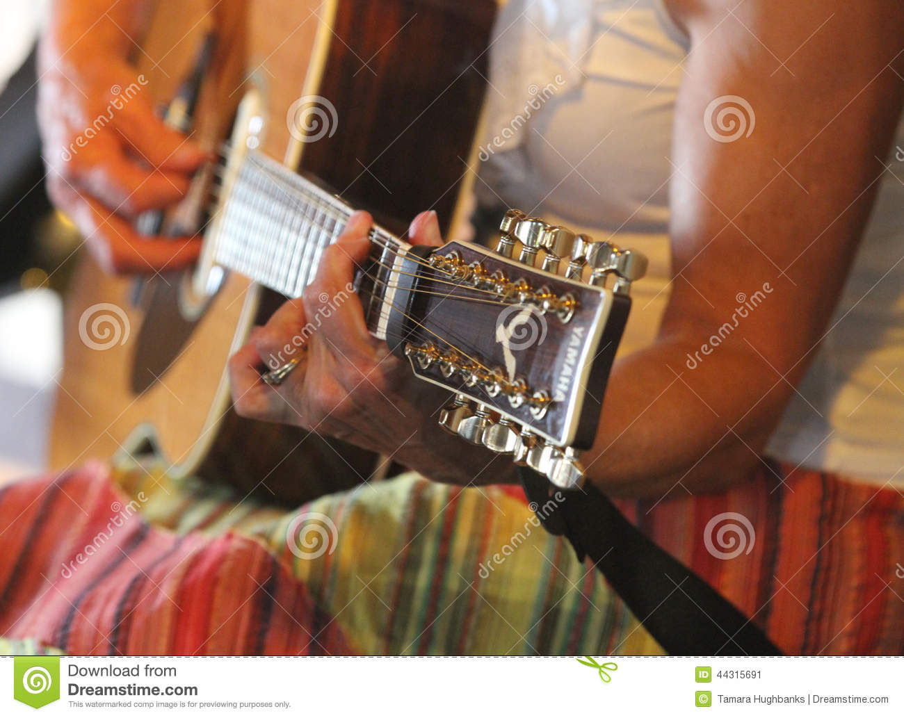 Beautiful female playing guitar in colorful skirt