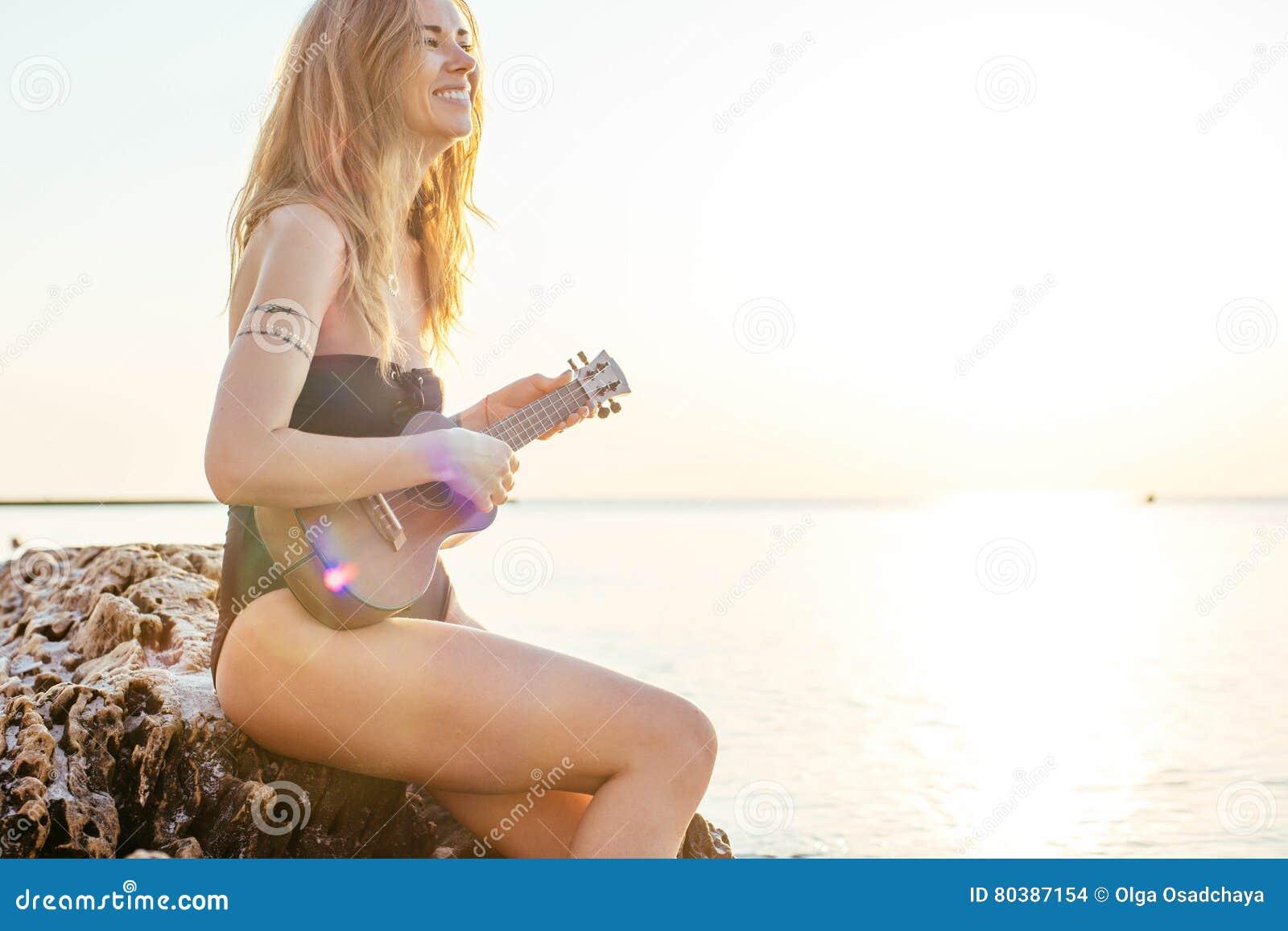 Beautiful female playing ukulele on beach