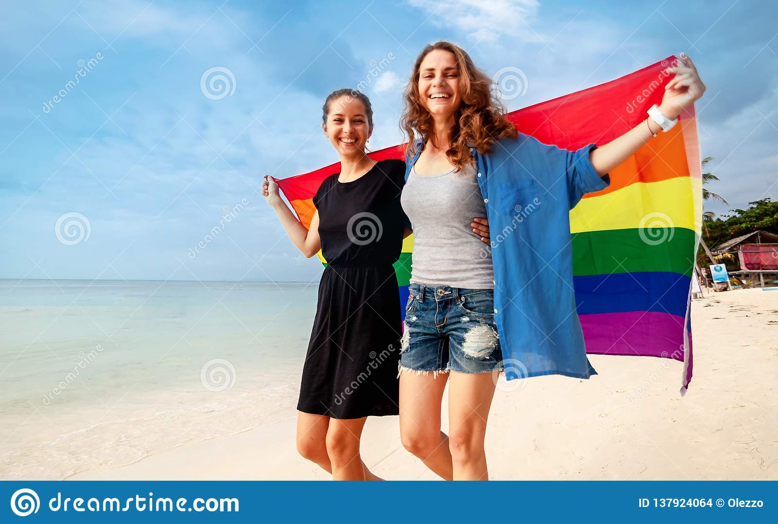 Beautiful female young lesbian couple in love walks along the beach with a rainbow flag, symbol of the LGBT community, equal