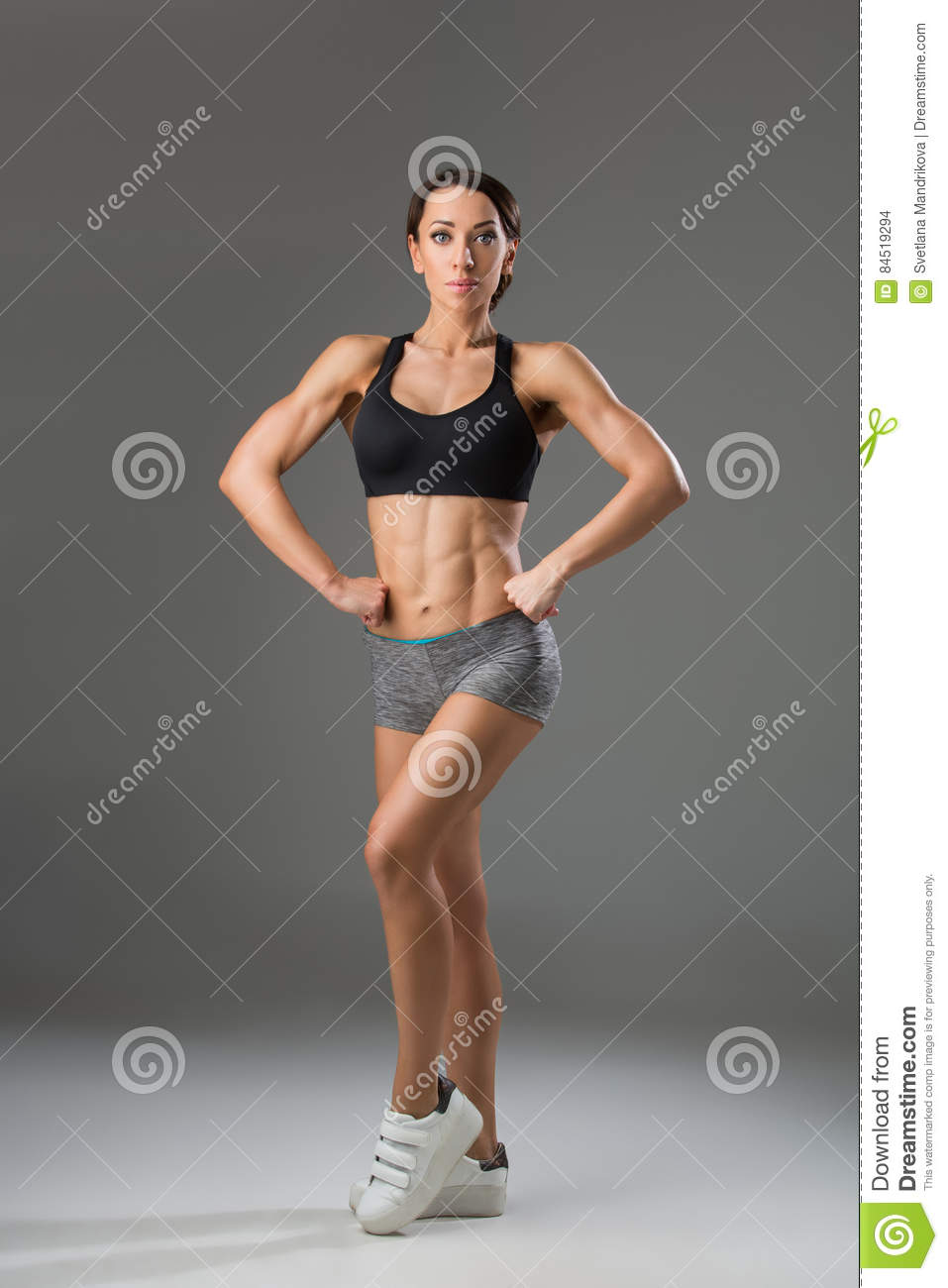 f5b67faa06 Beautiful fit muscular young woman in sport bra and shorts over grey  background. Perfect body. Studio shot. Copy space.