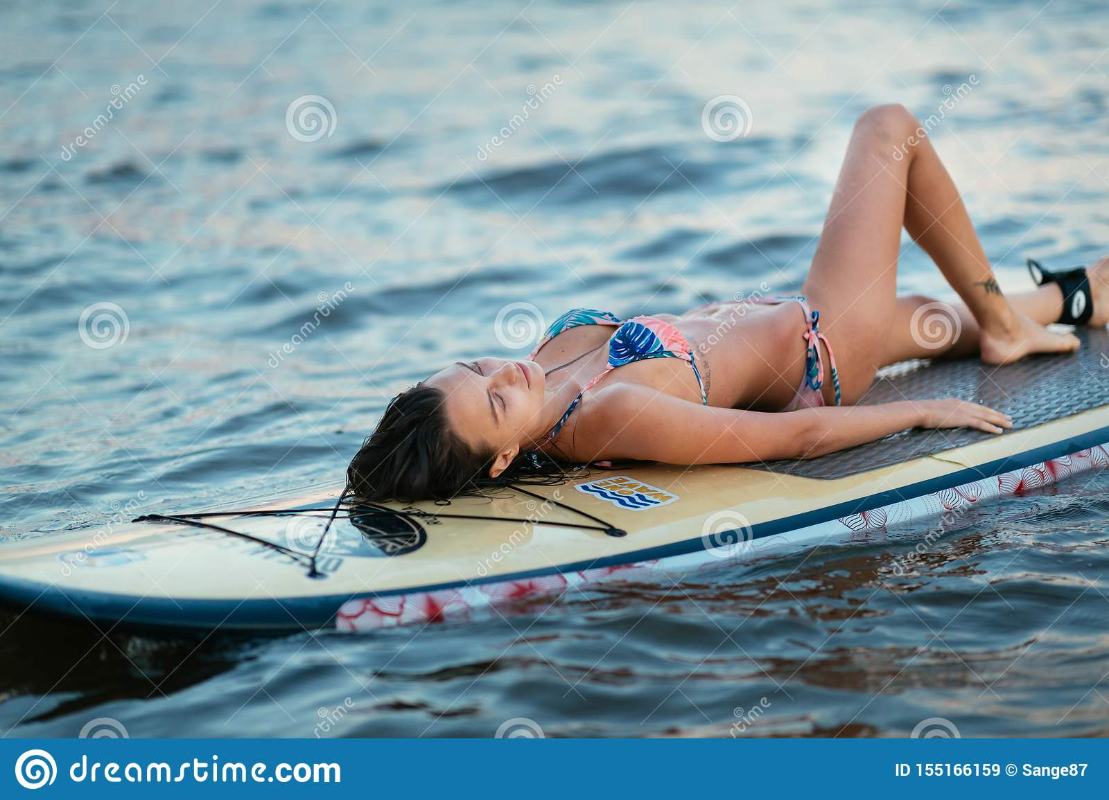 Beautiful Fit Surfing Girl On Surfboard On In The Ocean