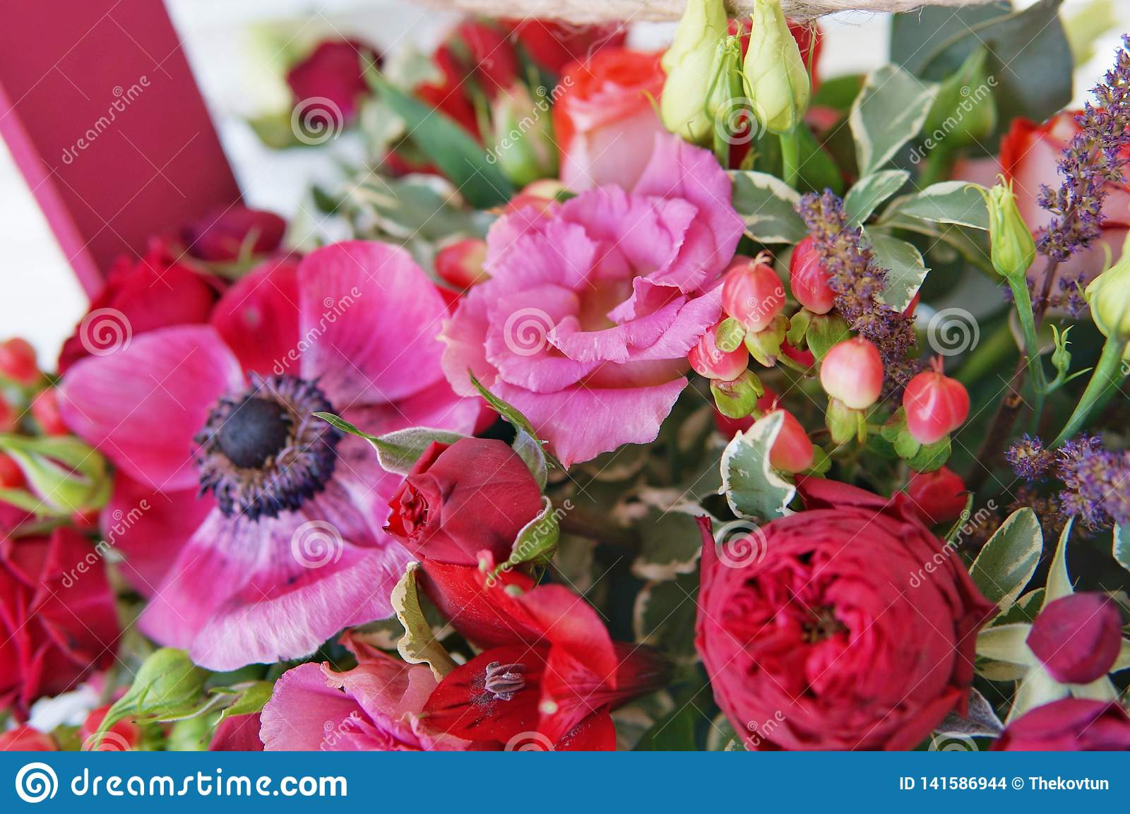 Beautiful floral arrangement of red, pink and burgundy flowers in a pink wooden box