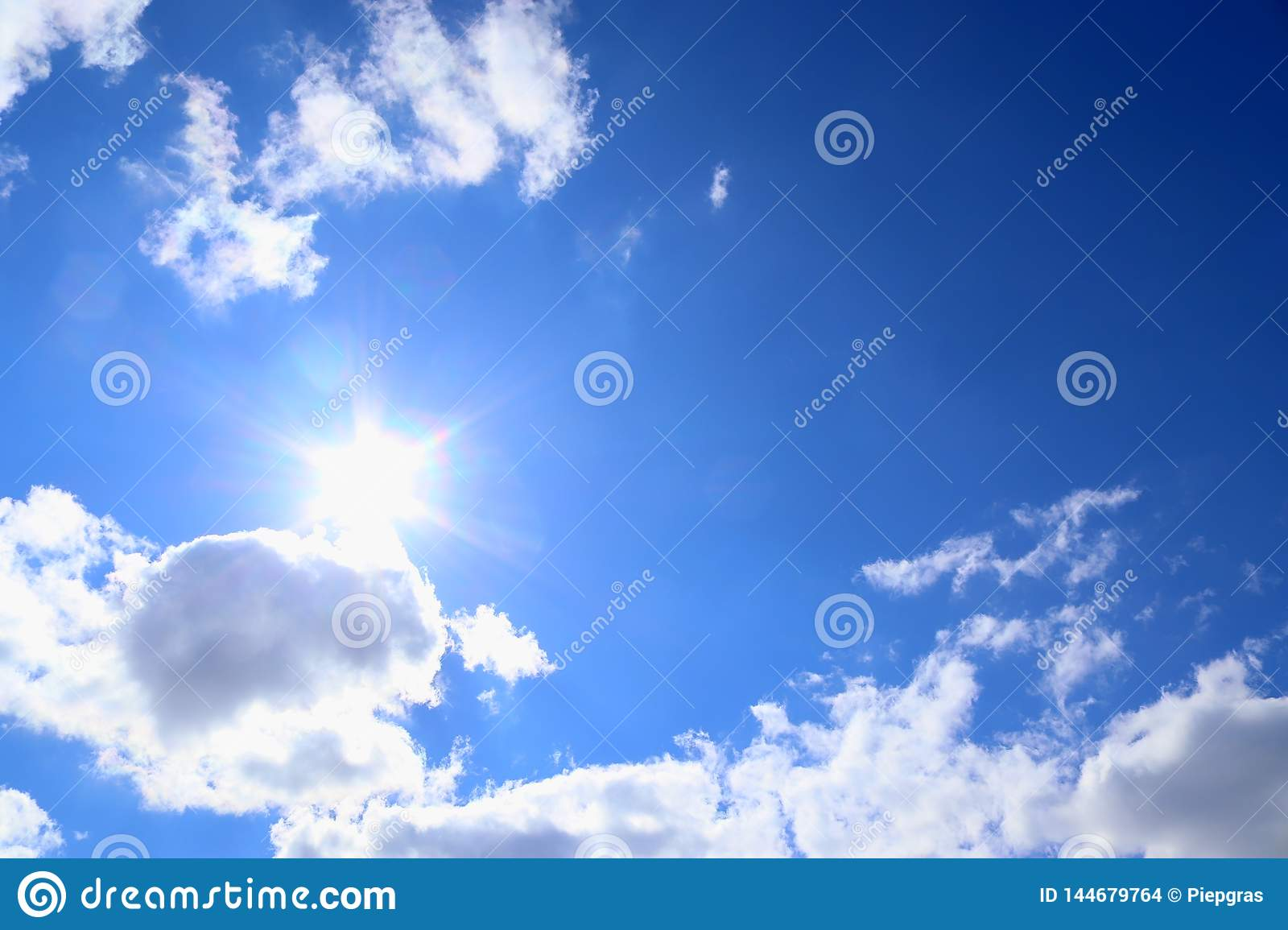 Beautiful fluffy white cumulus and cirrus clouds on a deep blue sky