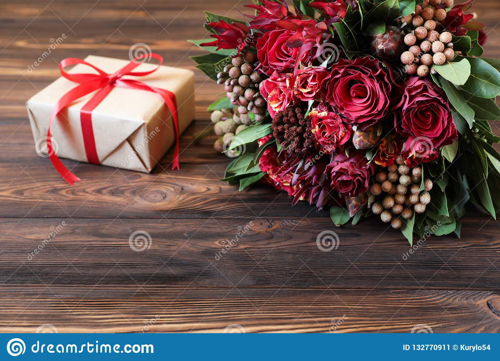 Beautiful fresh flower arrangement of red roses and gift box.