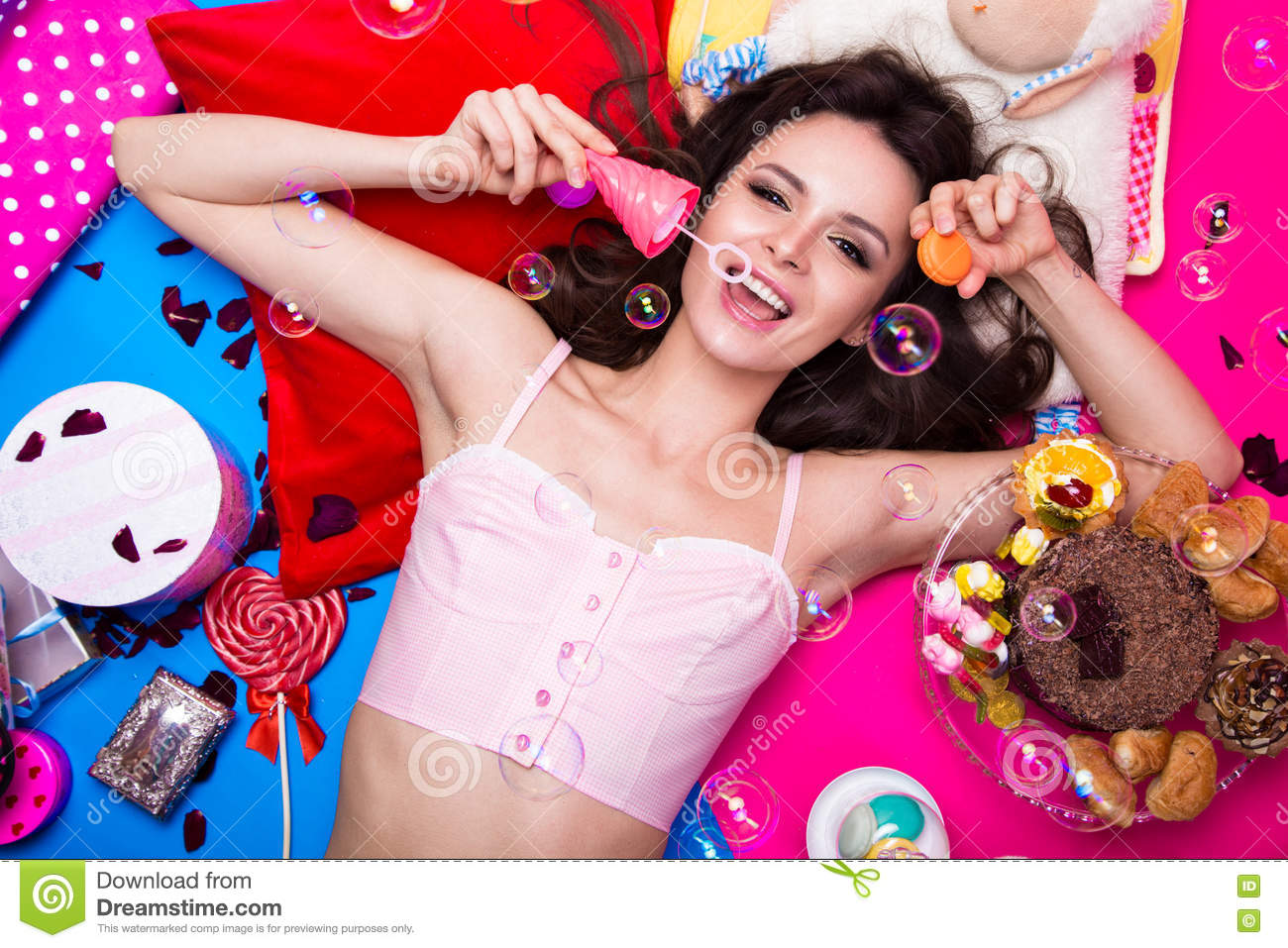 Beautiful fresh girl doll with soap bubbles lying on bright backgrounds surrounded by sweets, cosmetics and gifts