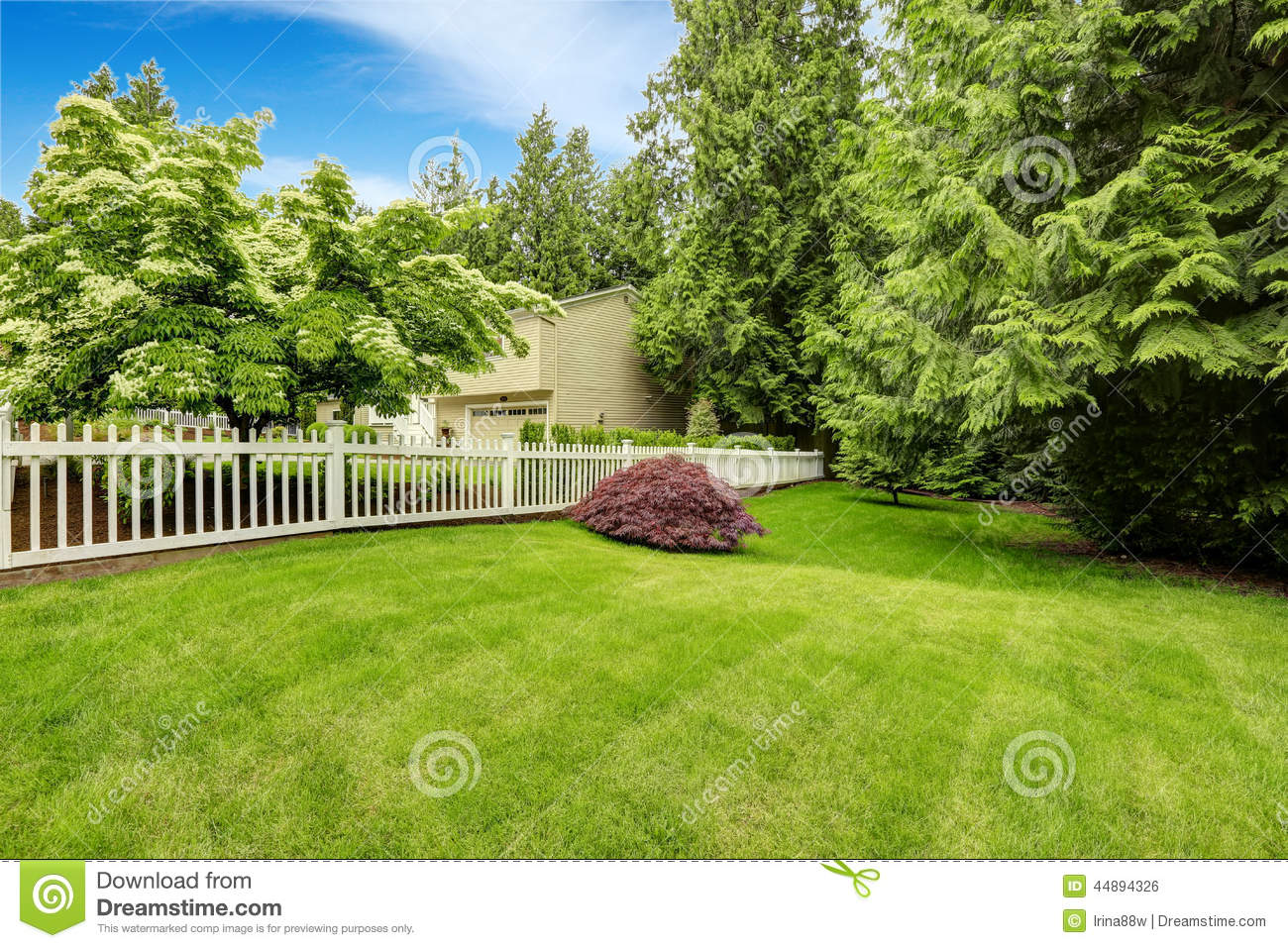 beautiful front yard landscape with white fence stock photo