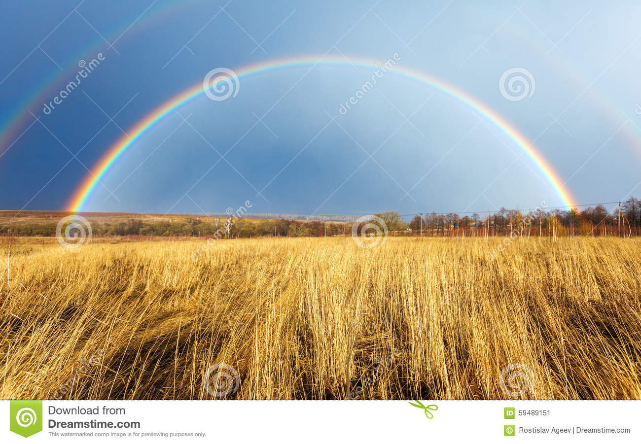 Beautiful Full Rainbow above Farm Field at Spring