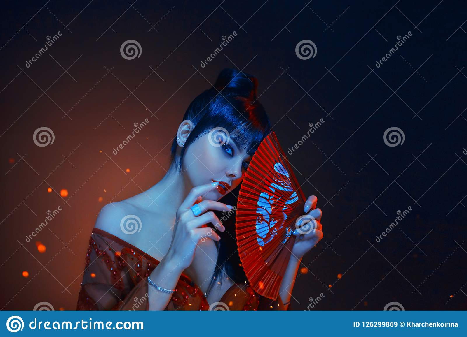 A beautiful geisha with blue long hair and a bang is looking in soul. red make up, lips, long dress with open shoders