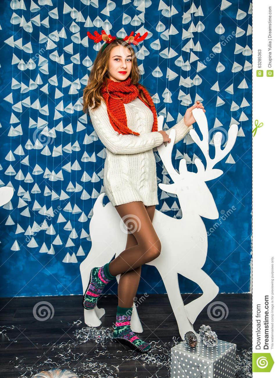 Beautiful girl on the background of blue wall with garlands and