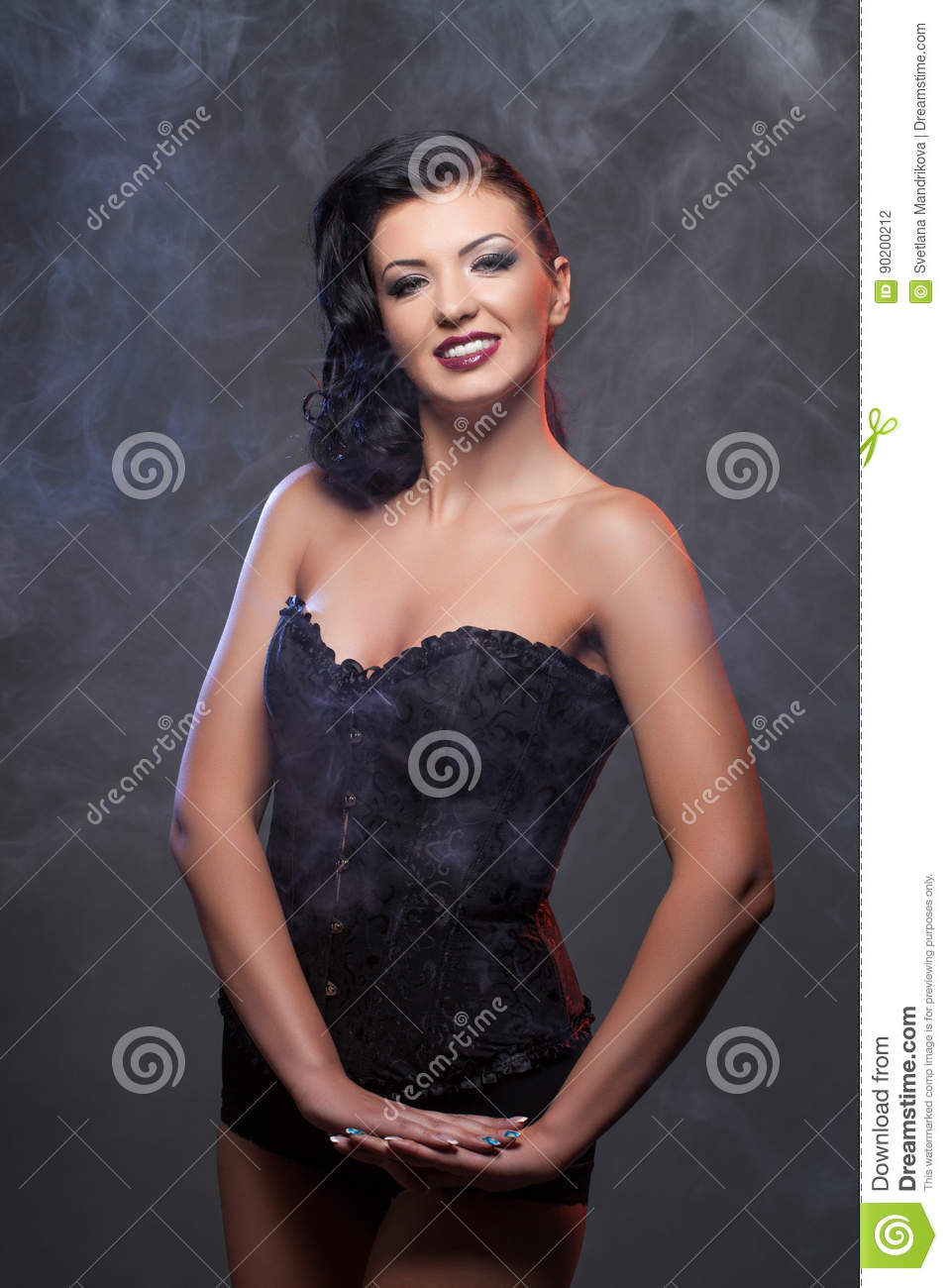 b70a7649dc1 Beautiful brunette young woman in black corset on dark background. Copy  space.