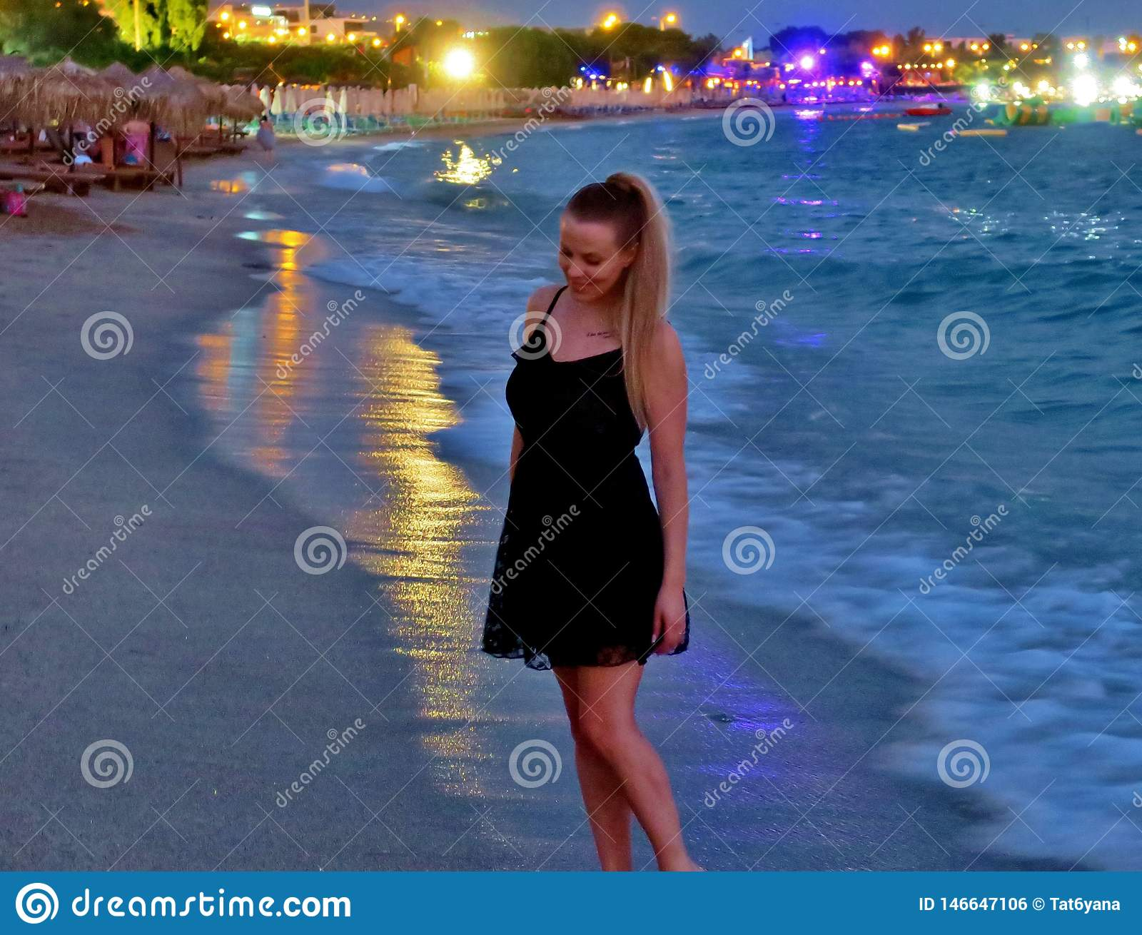 Beautiful girl in a black dress by the sea
