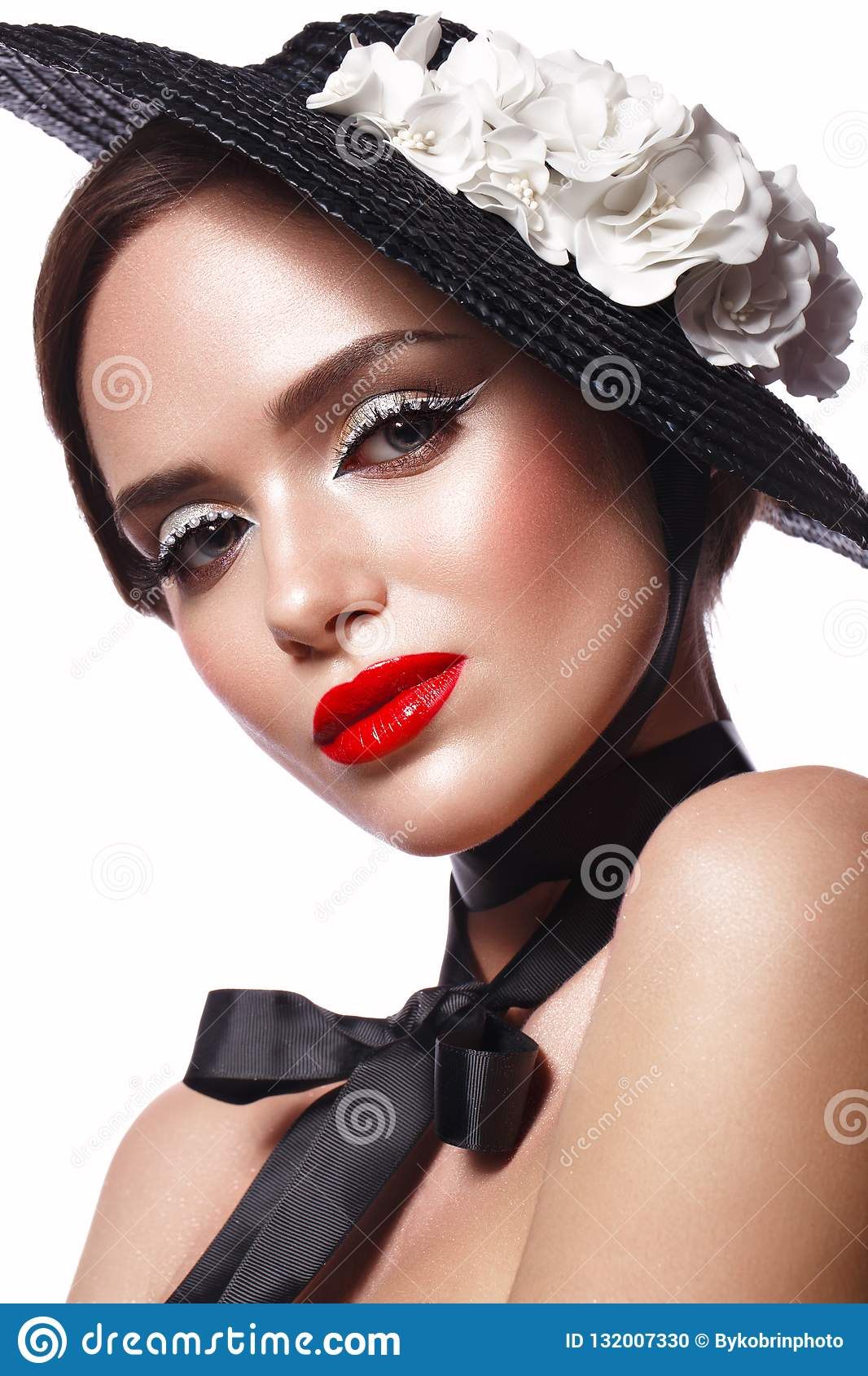 Beautiful girl in a black hat with flowers and retro makeup. Beauty face.