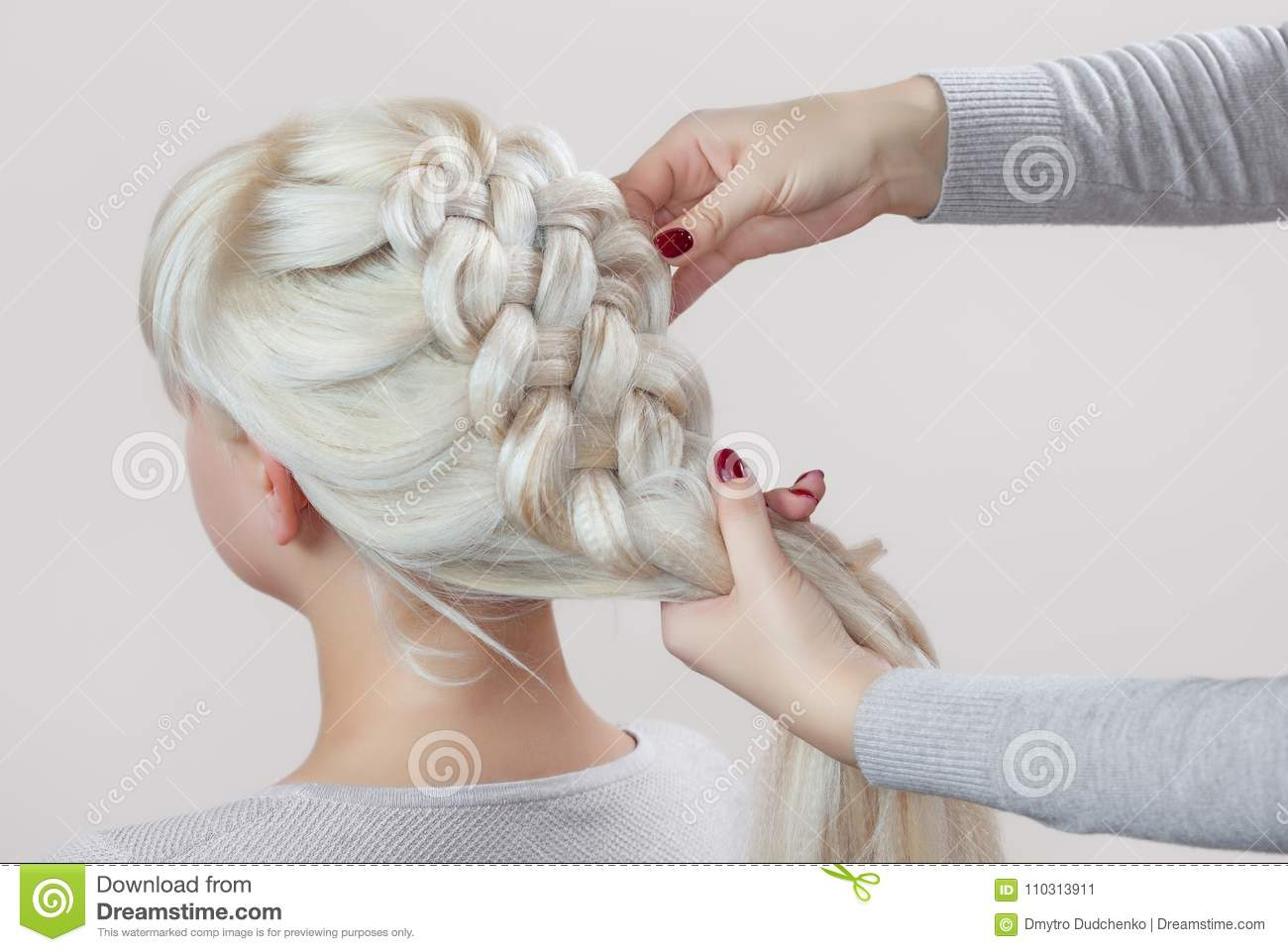 Beautiful girl with blonde hair, hairdresser weaves a braid close-up