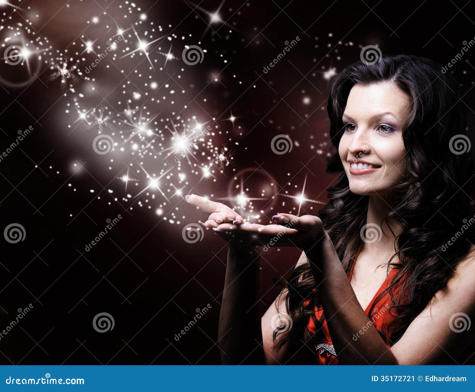Beautiful girl blowing magic