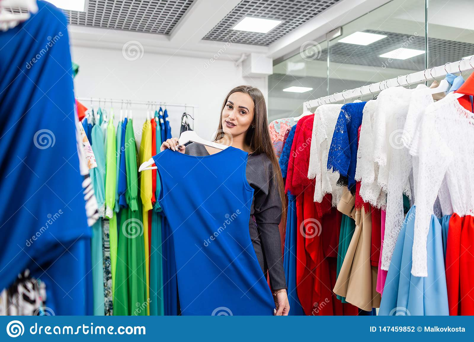 Beautiful girl with blue dress near mirror on room background. Happy young woman choosing clothes in mall or clothing