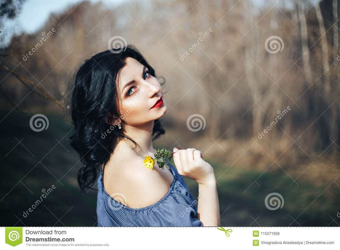 Beautiful girl in blue dress standing near spring garden against a  background of green grass and gray trees e98cc965b