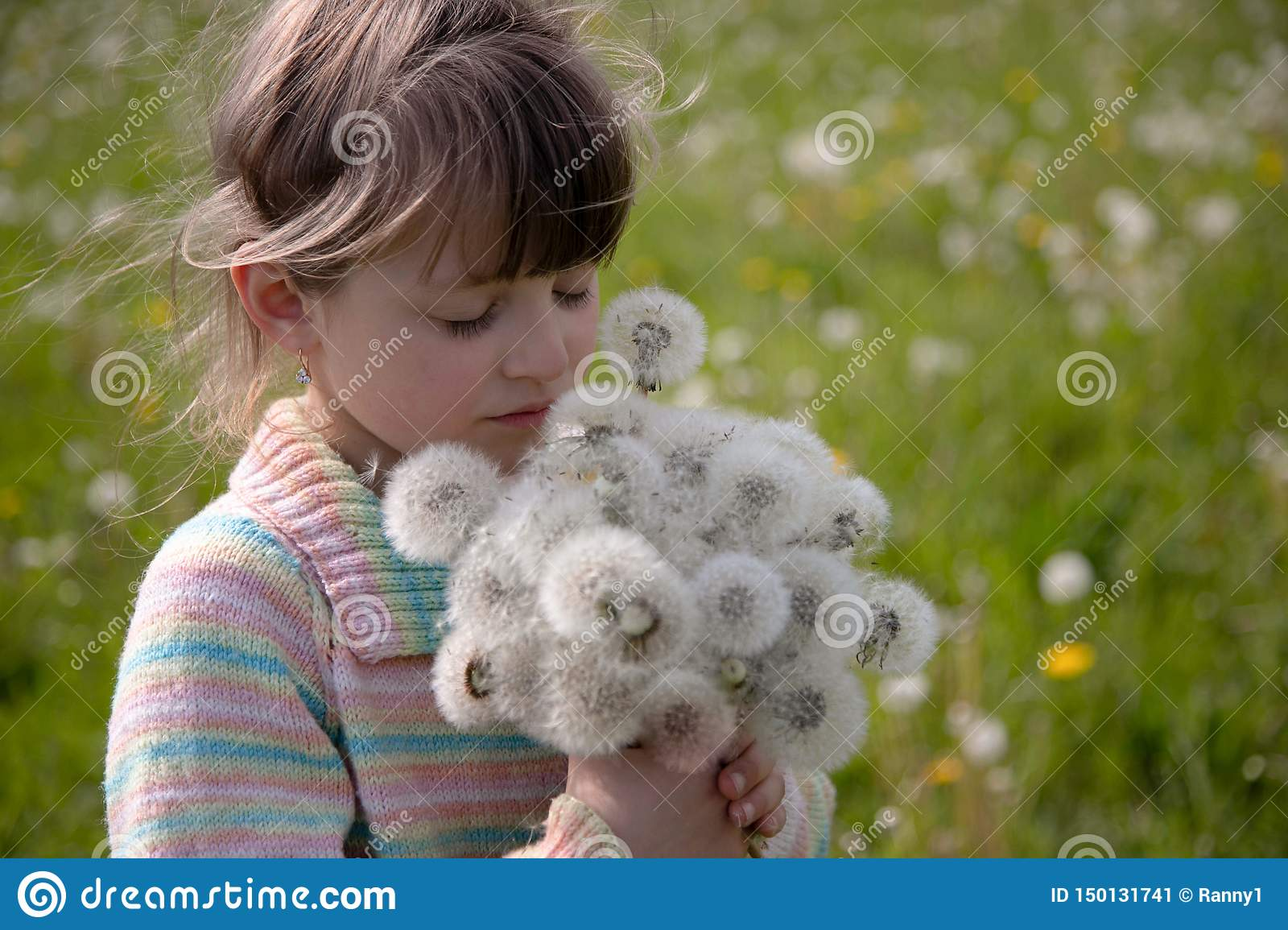 Beautiful girl with a bouquet of white dandelions on a spring meadow