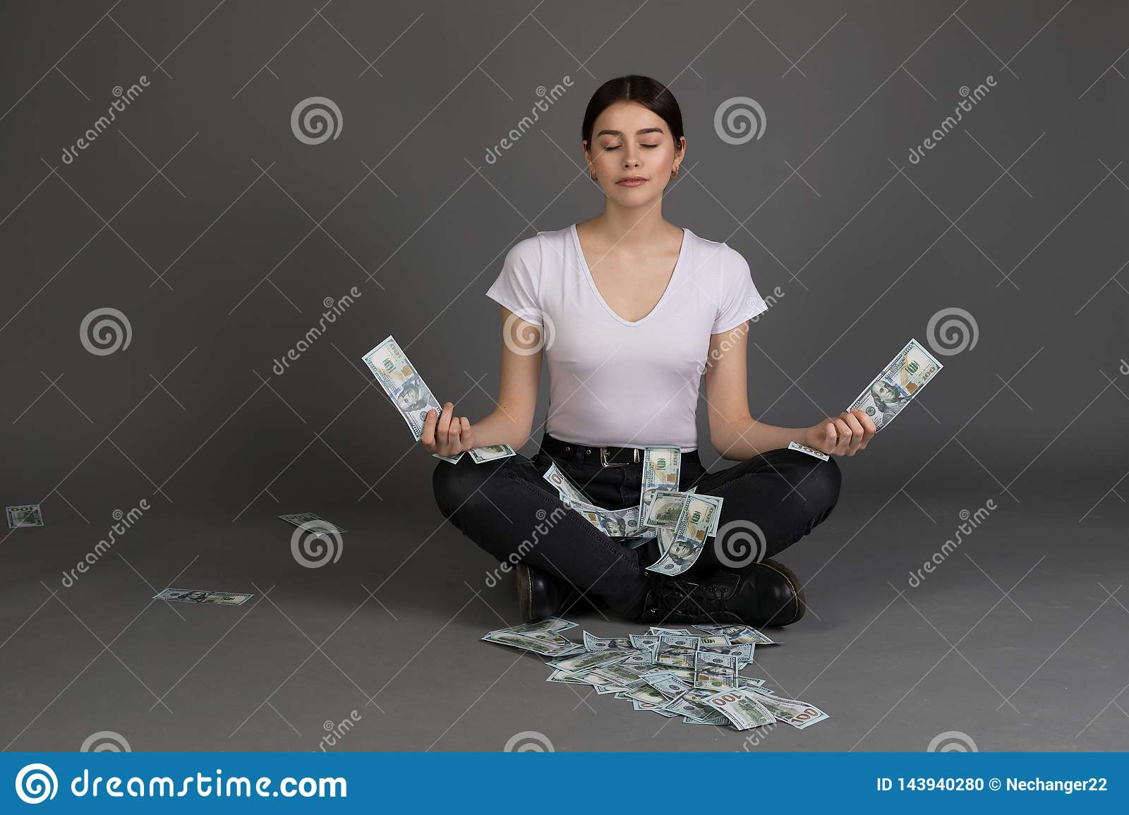 Beautiful girl with brunette hair in white t-shirt meditates with closed eyes while sitting in lotus position