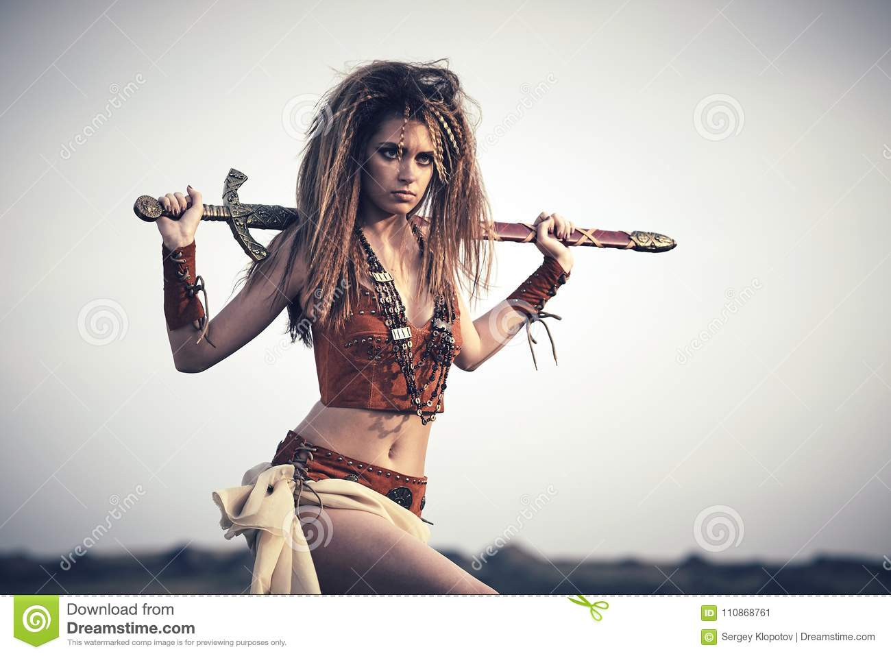 Beautiful girl in the clothes of a Viking or Amazon, with a sword on a background of sky.