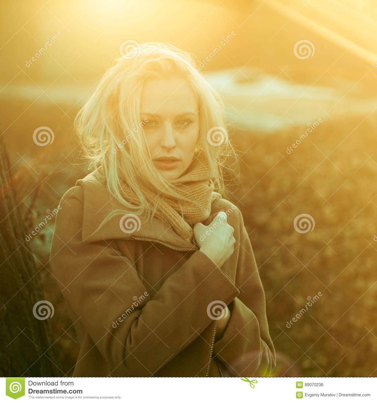 Beautiful girl in a coat posing against the background of a spring nature