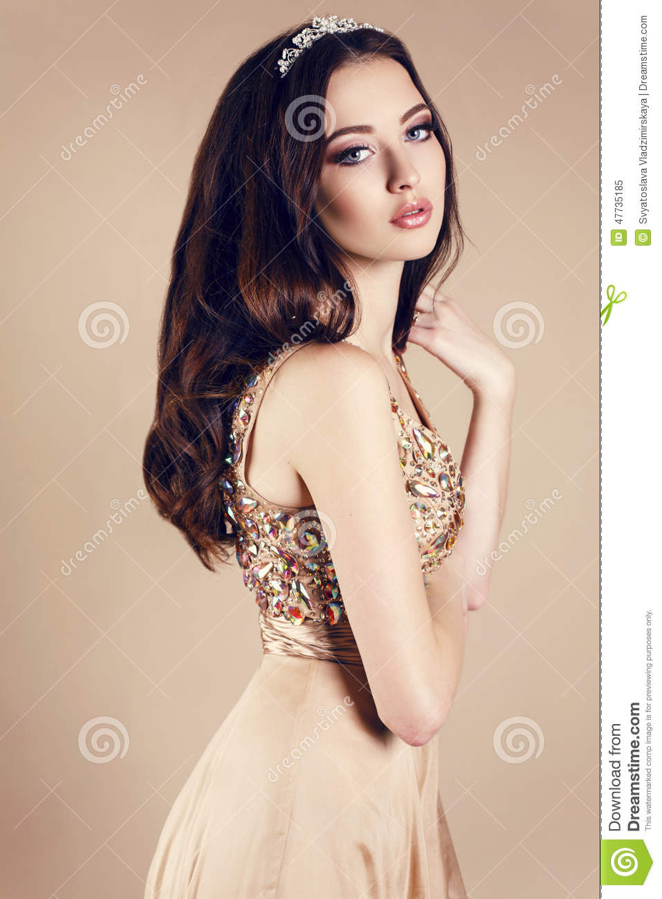 Beautiful girl with dark hair in luxurious sequin dress and crown