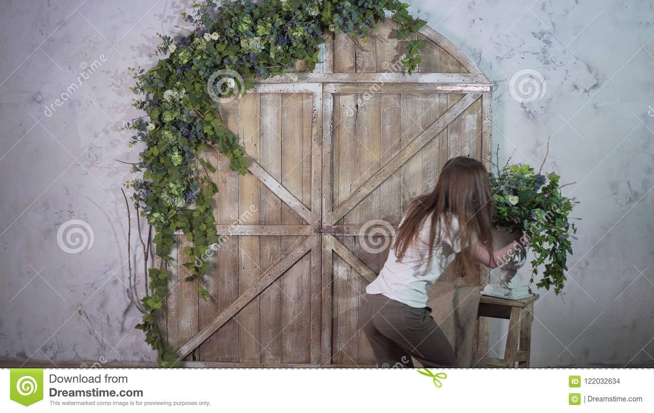 Beautiful girl decorator carries a vase of flowers and puts on a vintage small staircase against a beautiful photozone