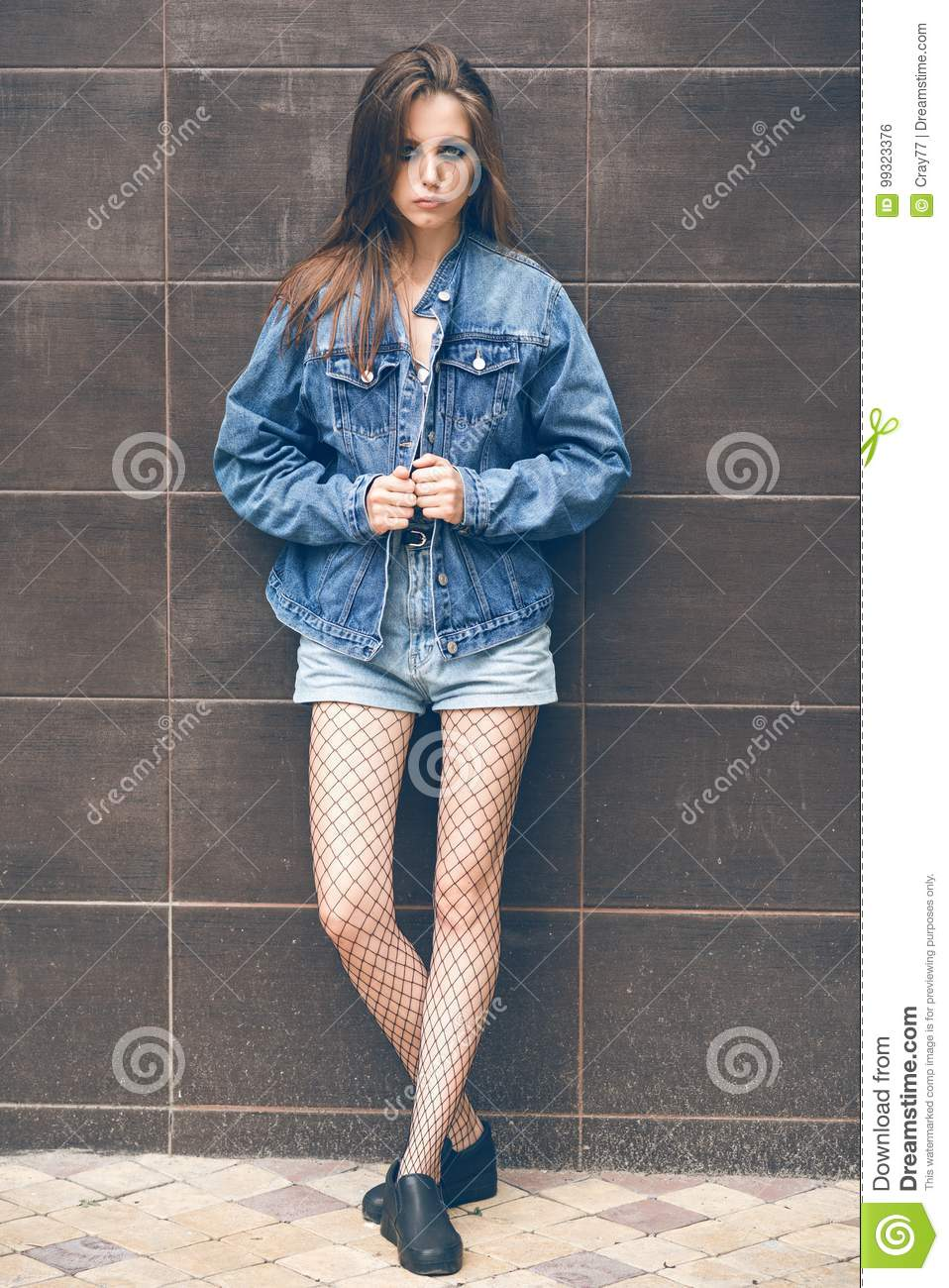 b2722df8a01 Beautiful girl in denim shorts and jeans jacket in the street. Rock style. Fashionable  girl. Dark background. Beautiful