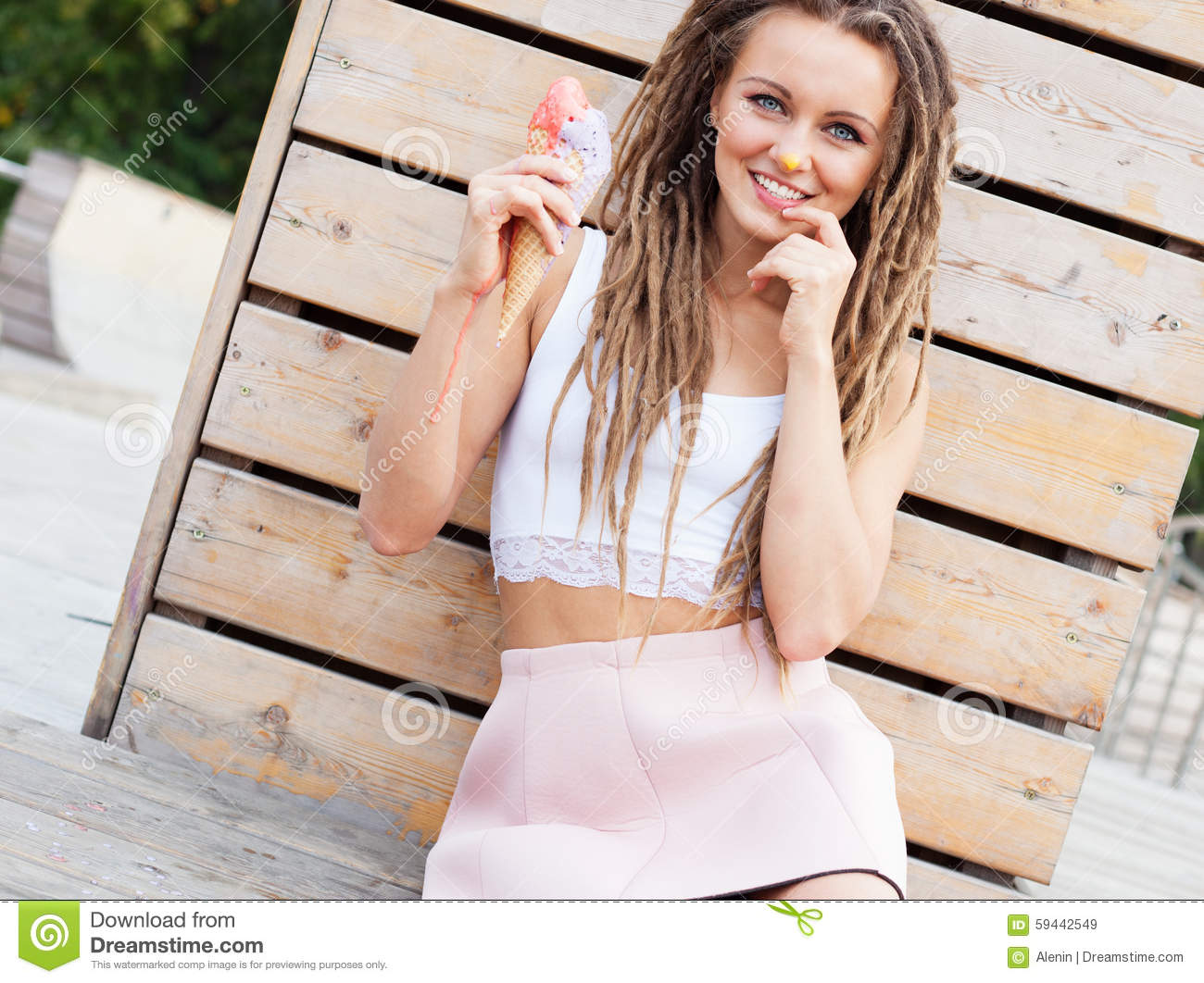 Beautiful girl with dreadlocks in pink skirt sitting on the veranda and eating colorful ice-cream cone on a warm summer evening.