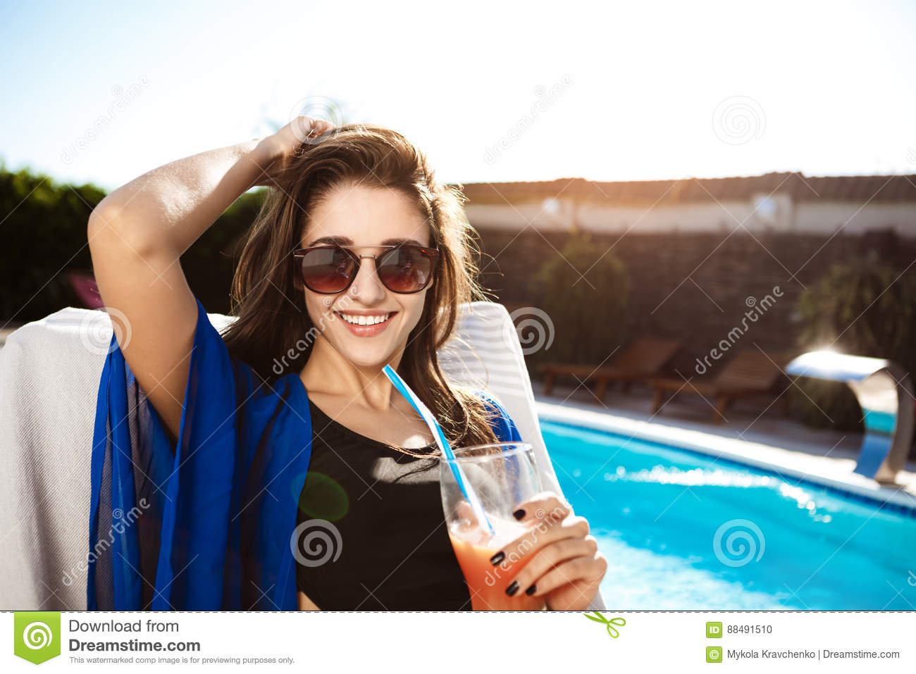 Beautiful girl drinking cocktail, lying on chaise near swimming pool.