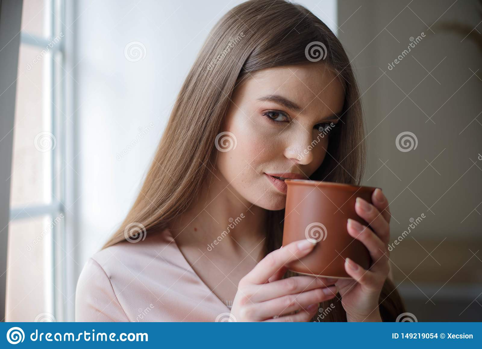 Beautiful girl is drinking coffee and smiling while sitting at the cafe