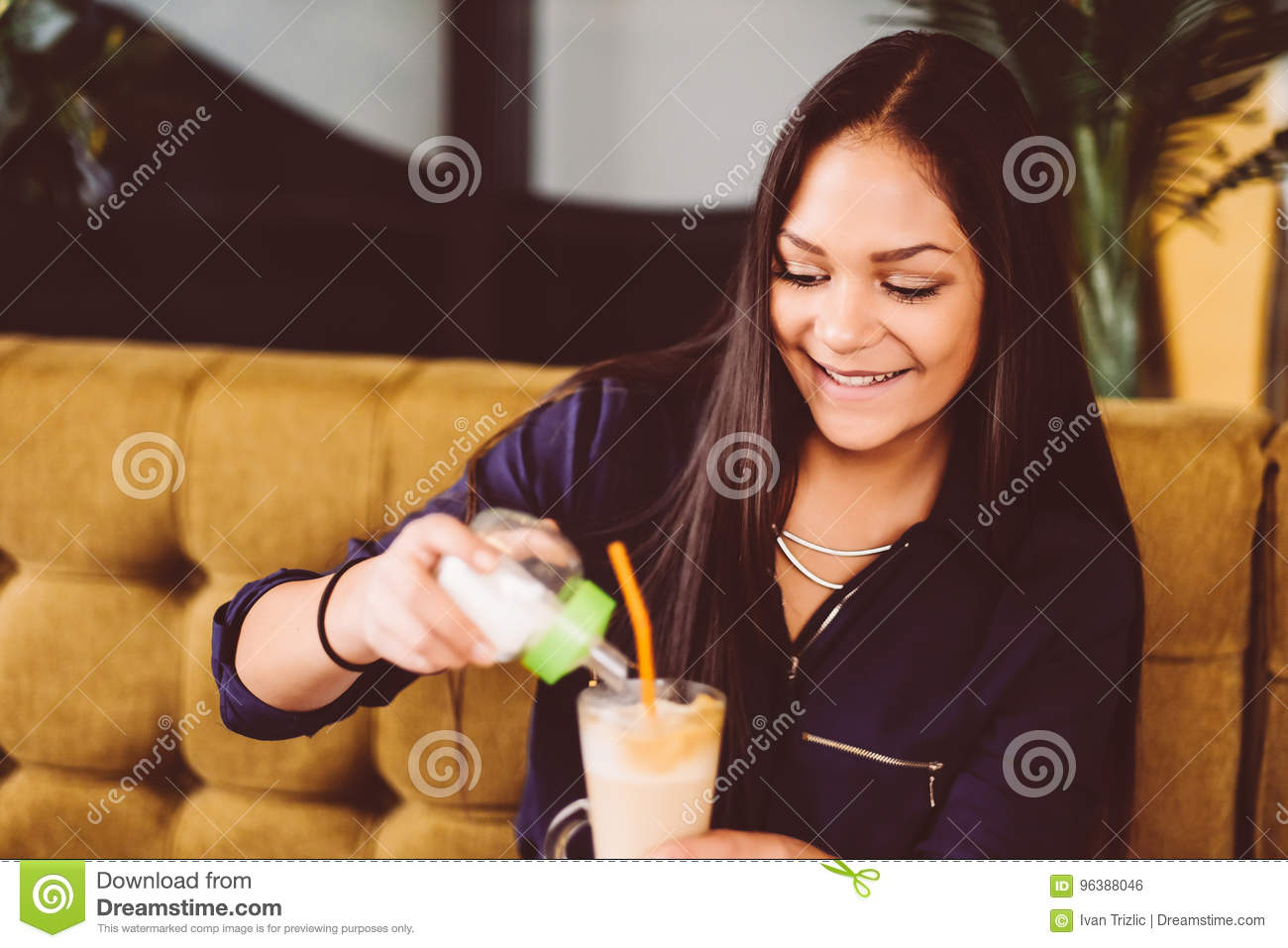 Beautiful girl drinking ice mocha shake in a cafe