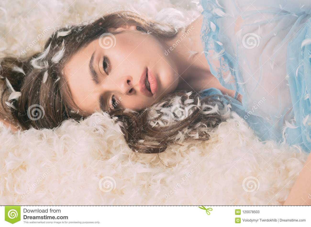 Beautiful girl drowning in soft bed. Drowsy young lady falling asleep, resting on downy white feathers, coziness concept