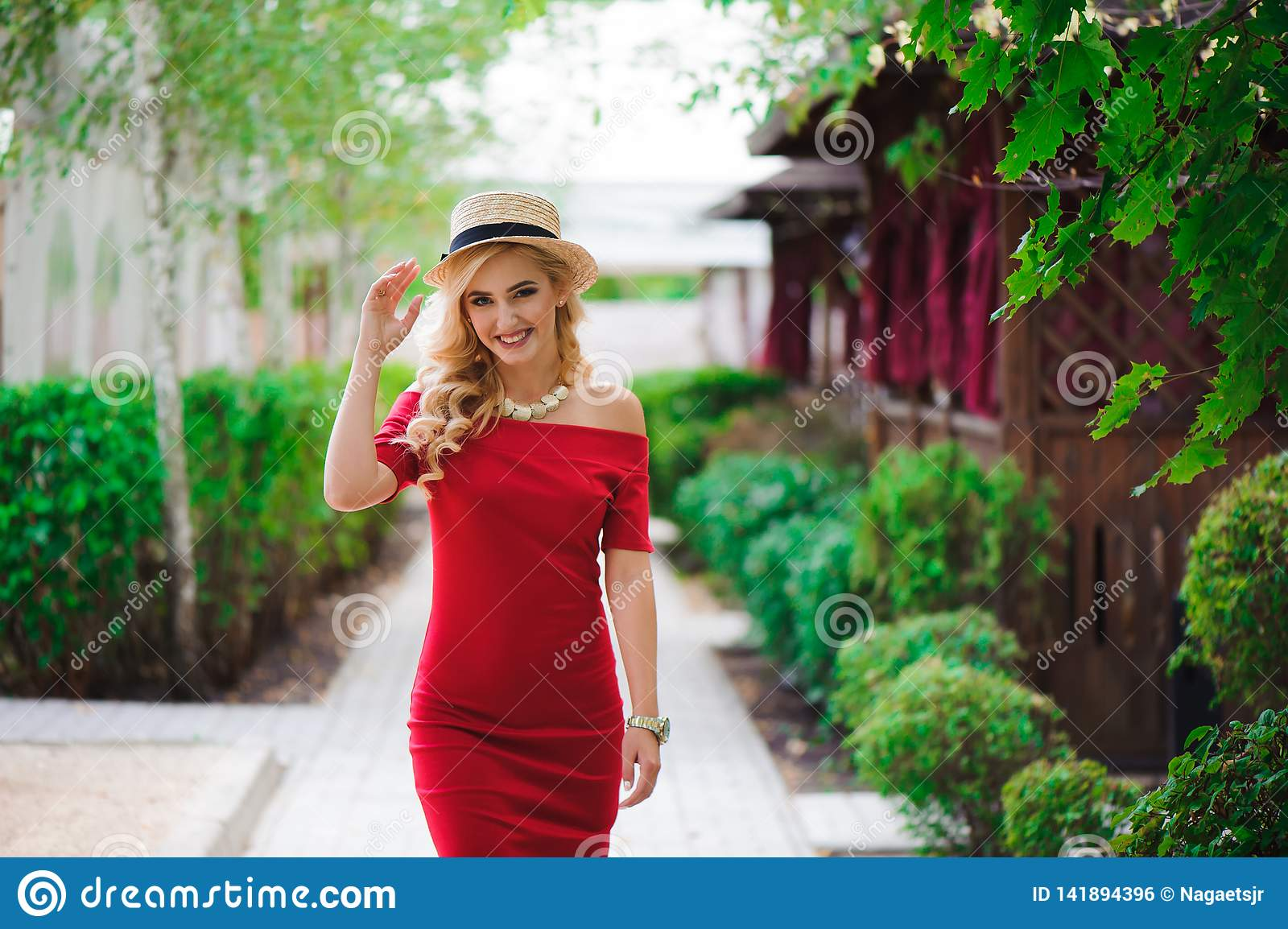 Beautiful girl in elegant dress and hat and charming smile posing for the photographer in the park.