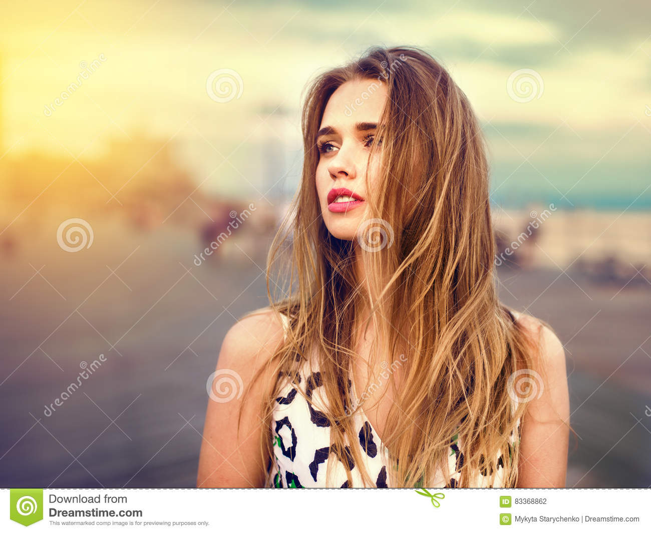 Beautiful girl enjoy the walk on the beach boardwalk at sunset time. Woman looking to the side outdoors
