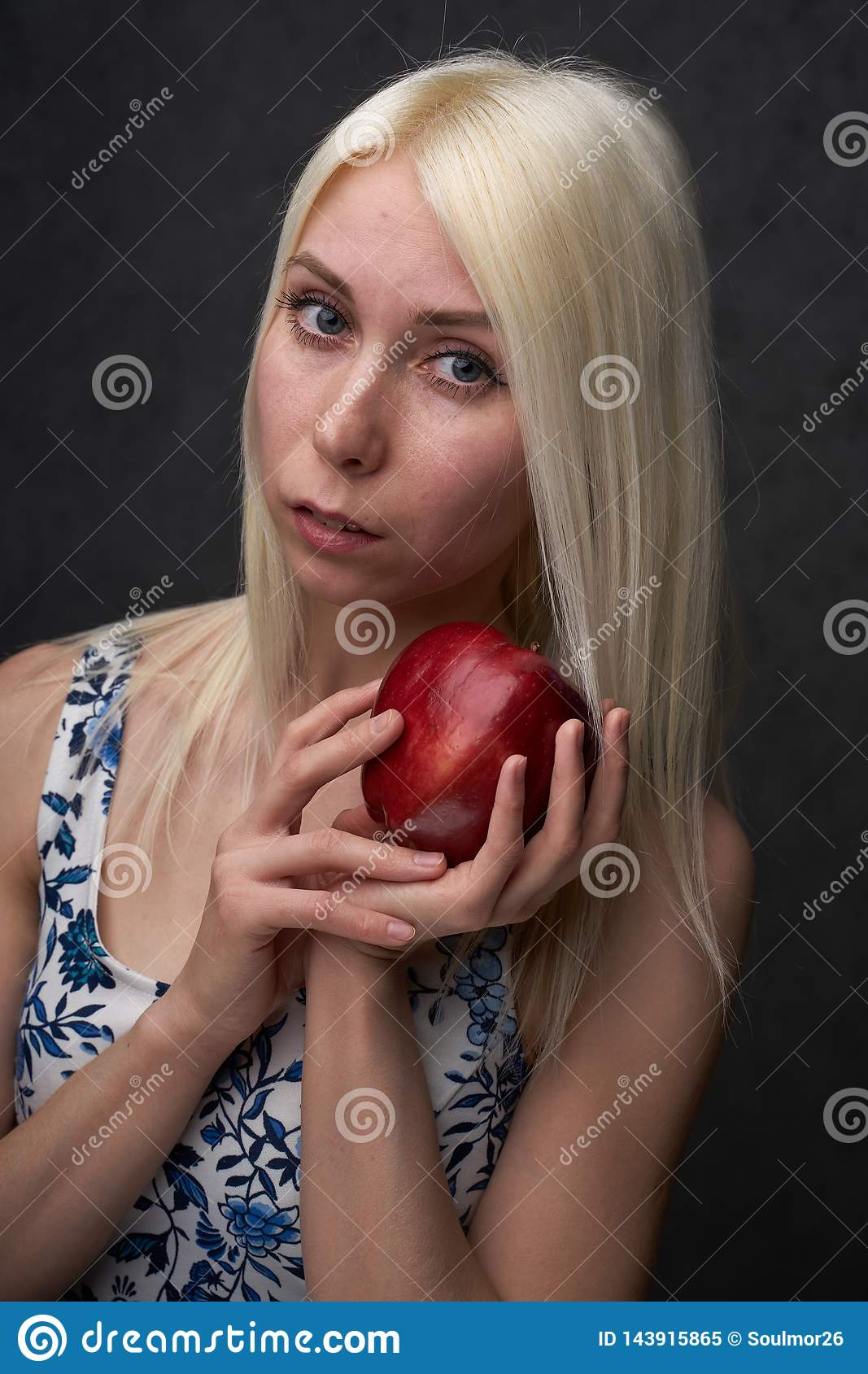 Beautiful girl in a fashionable dress with apple