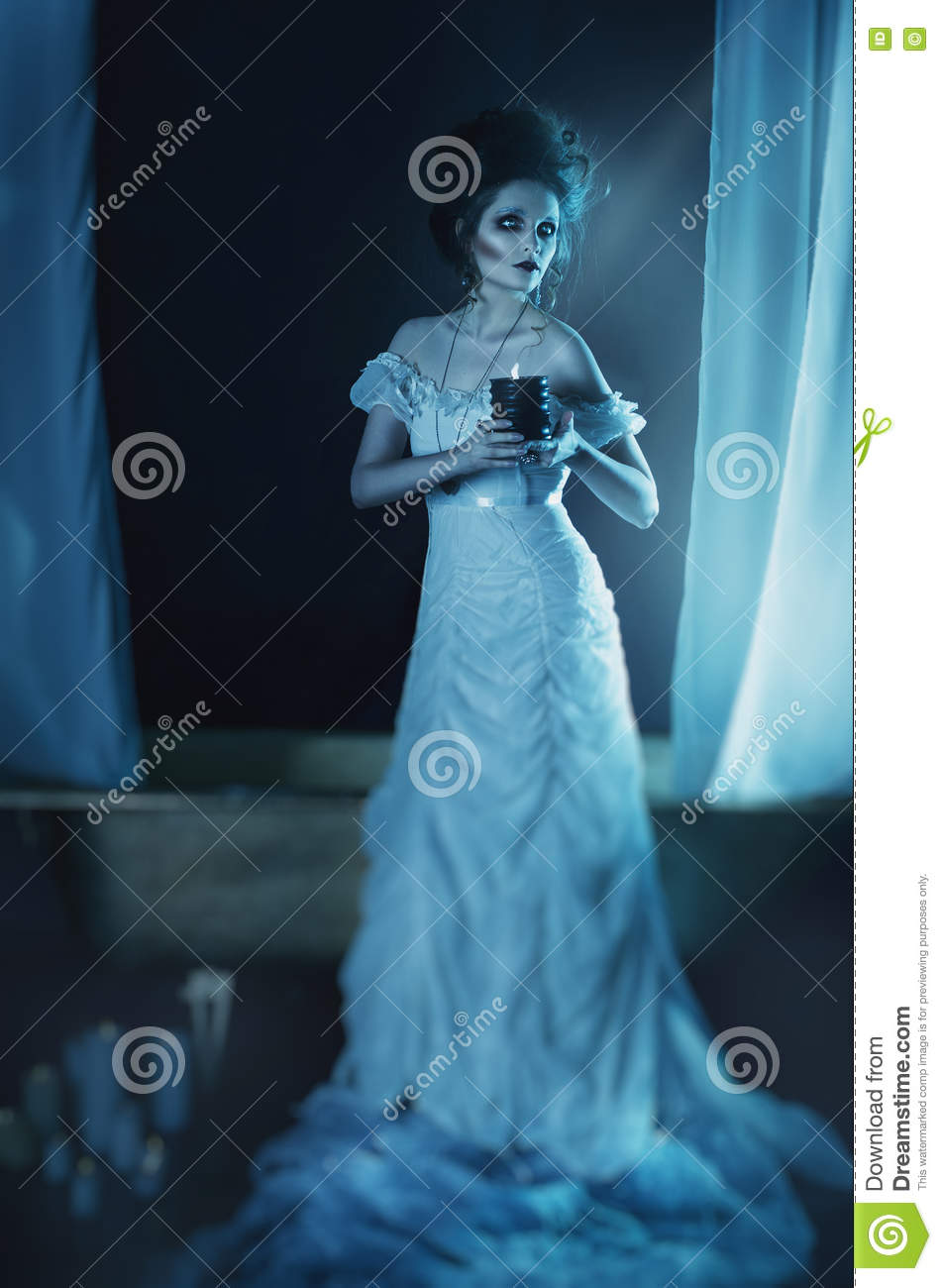 Beautiful girl ghost, witch bride in a white dress holding a black burning candle in hands