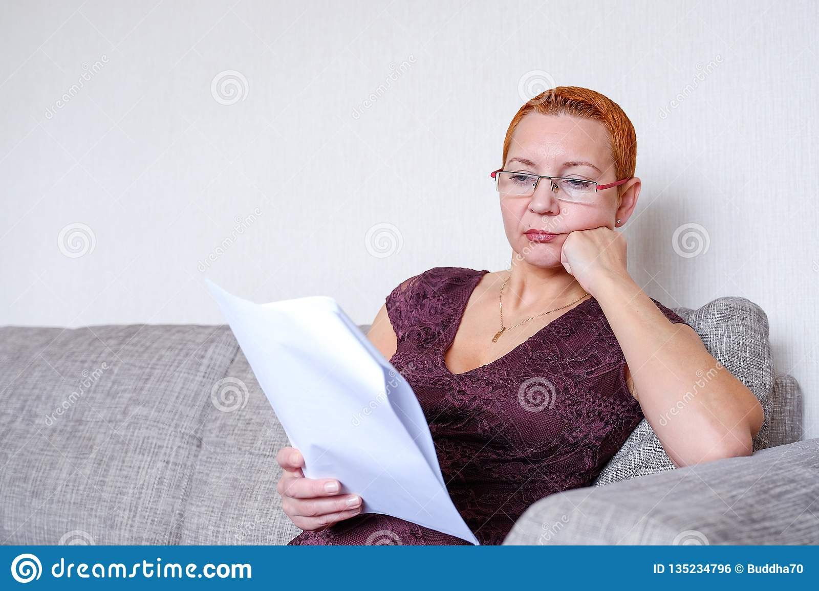 Beautiful girl with glasses looking through tax documents. Emotion of concentration. Serious regulations