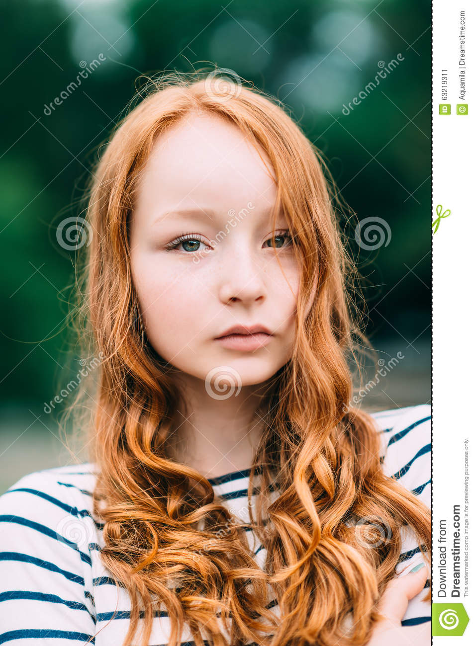 A Beautiful Girl With Green Eyes And Long Curly Red Hair