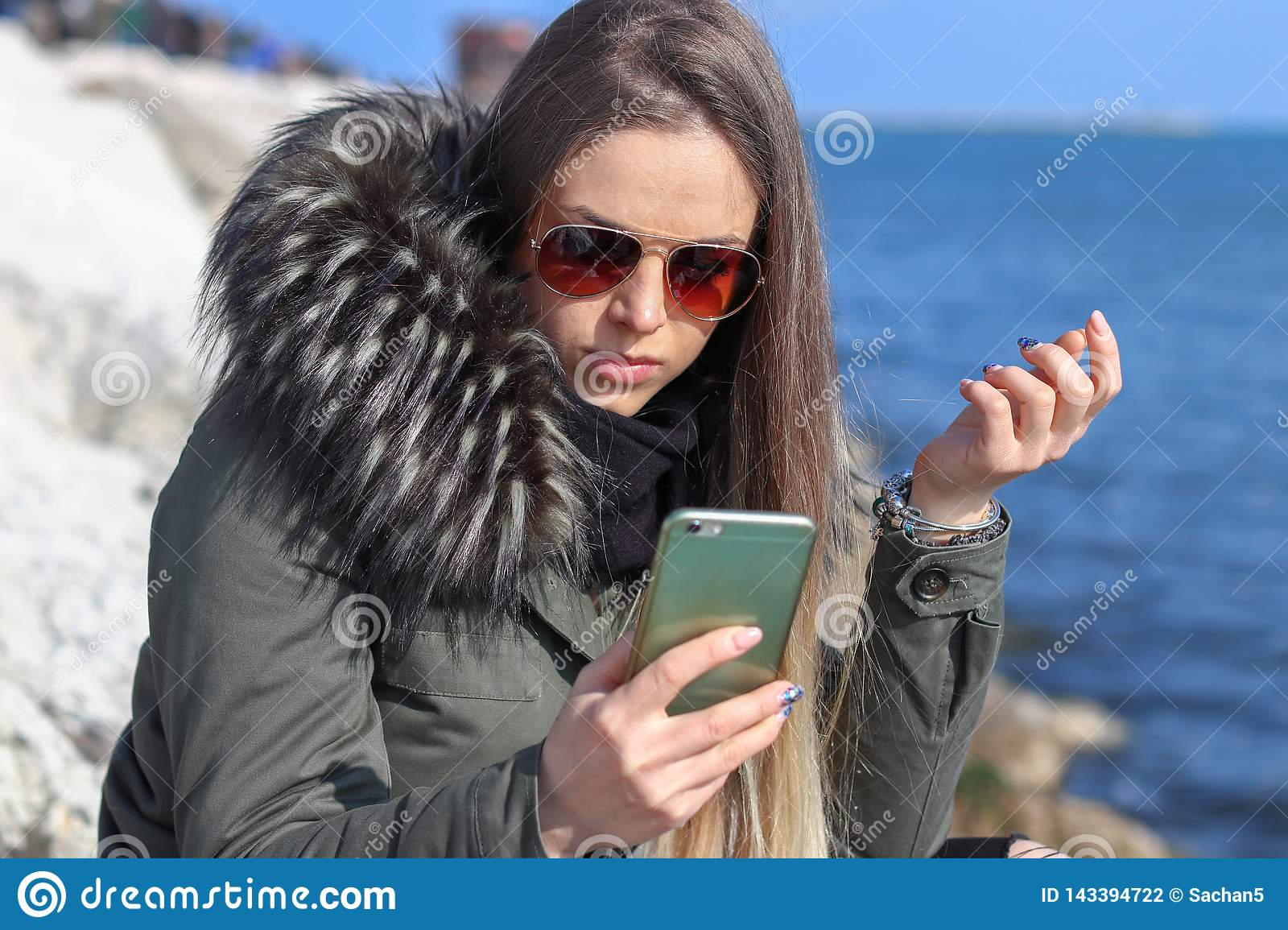 Beautiful girl. Happy woman looking to the phone on the beach with the sea in the background