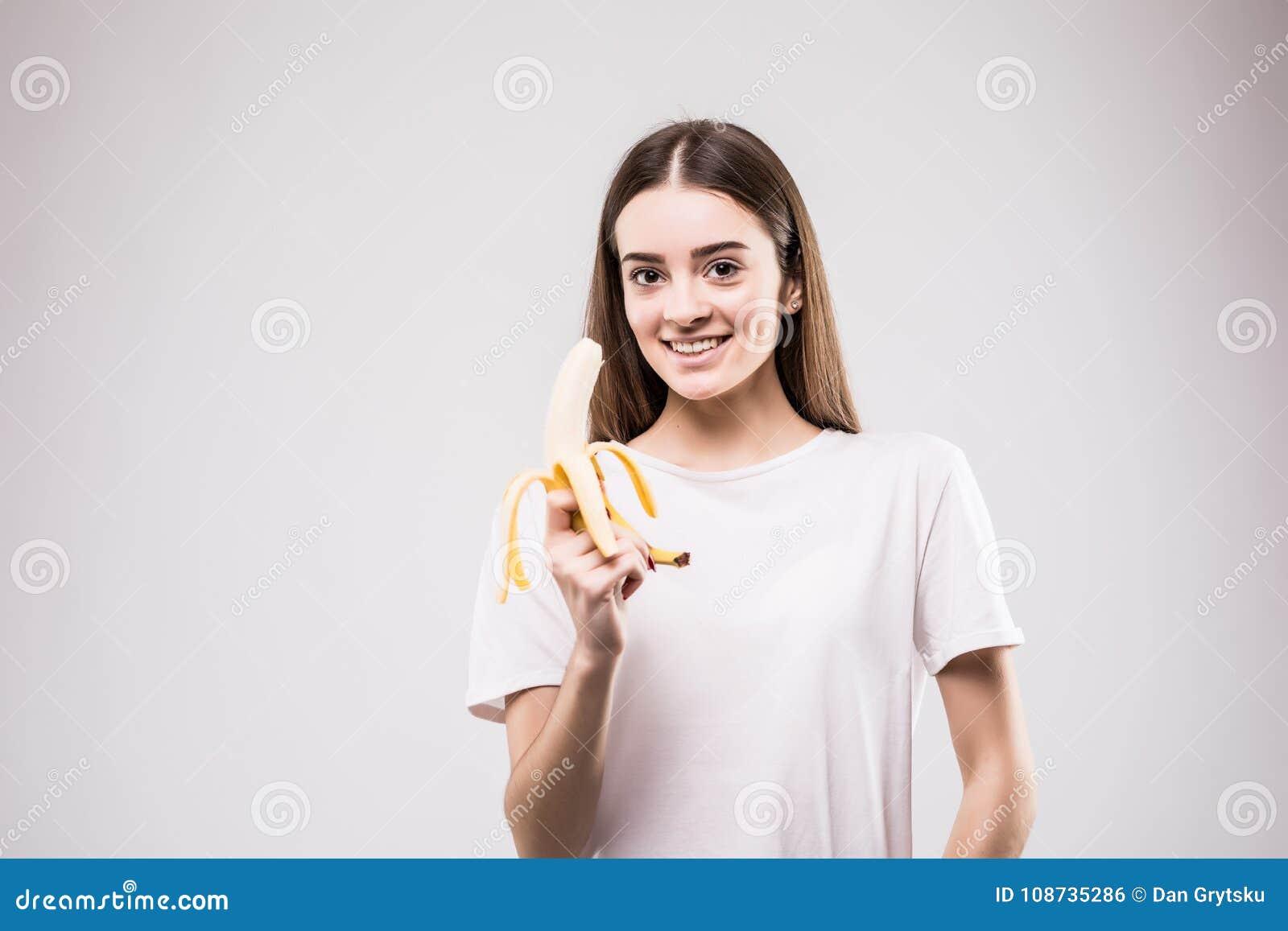 b399f0785092c Beautiful girl holding banana standing against isolated studio gray  background.