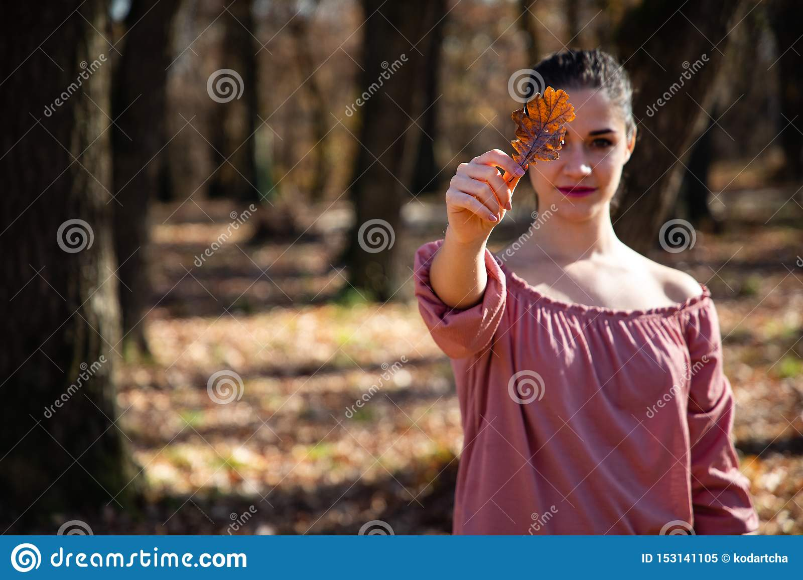 Beautiful girl holding a brown leaf covering her eye
