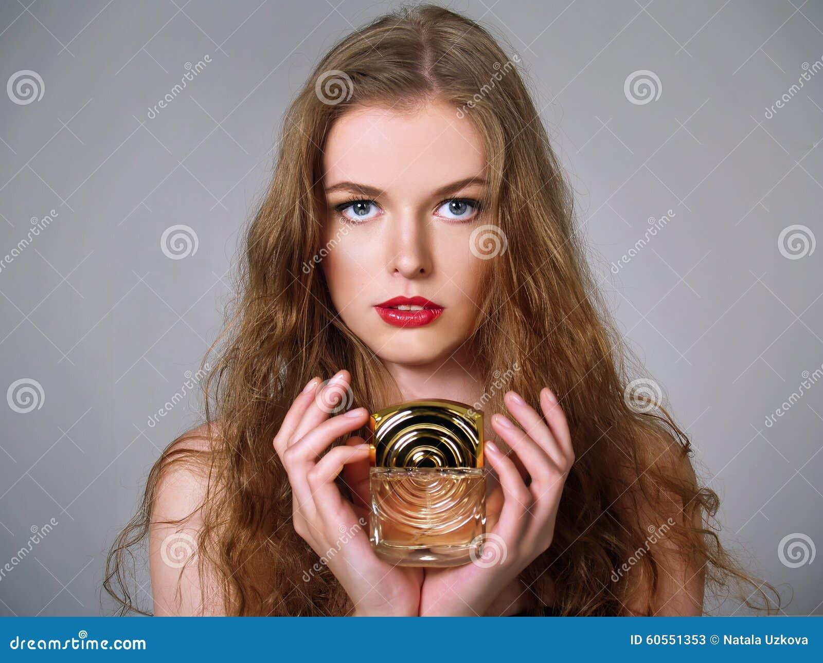 Beautiful girl holds perfumes
