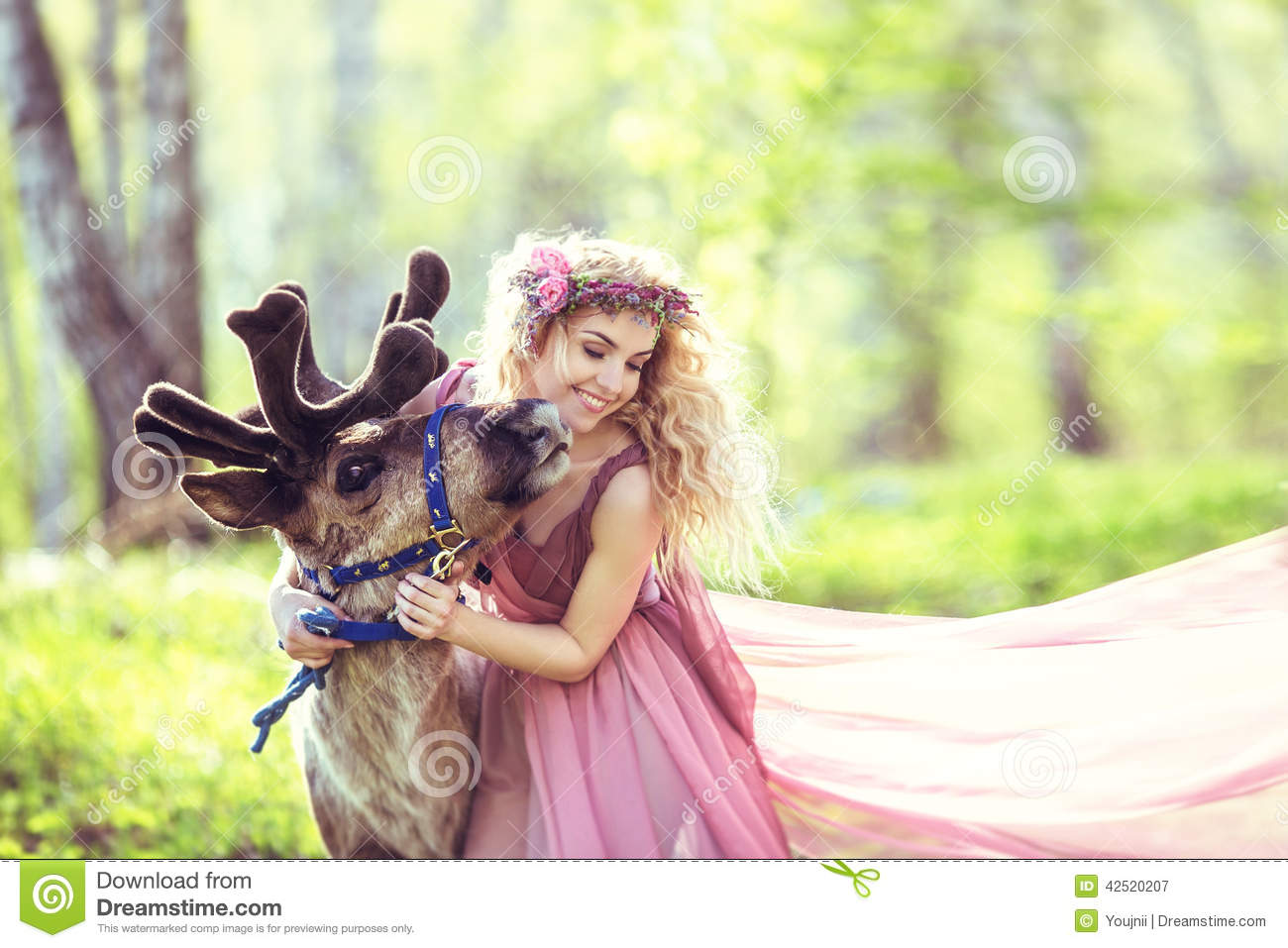 Beautiful Girl Hugging A Reindeer In The Forest Stock